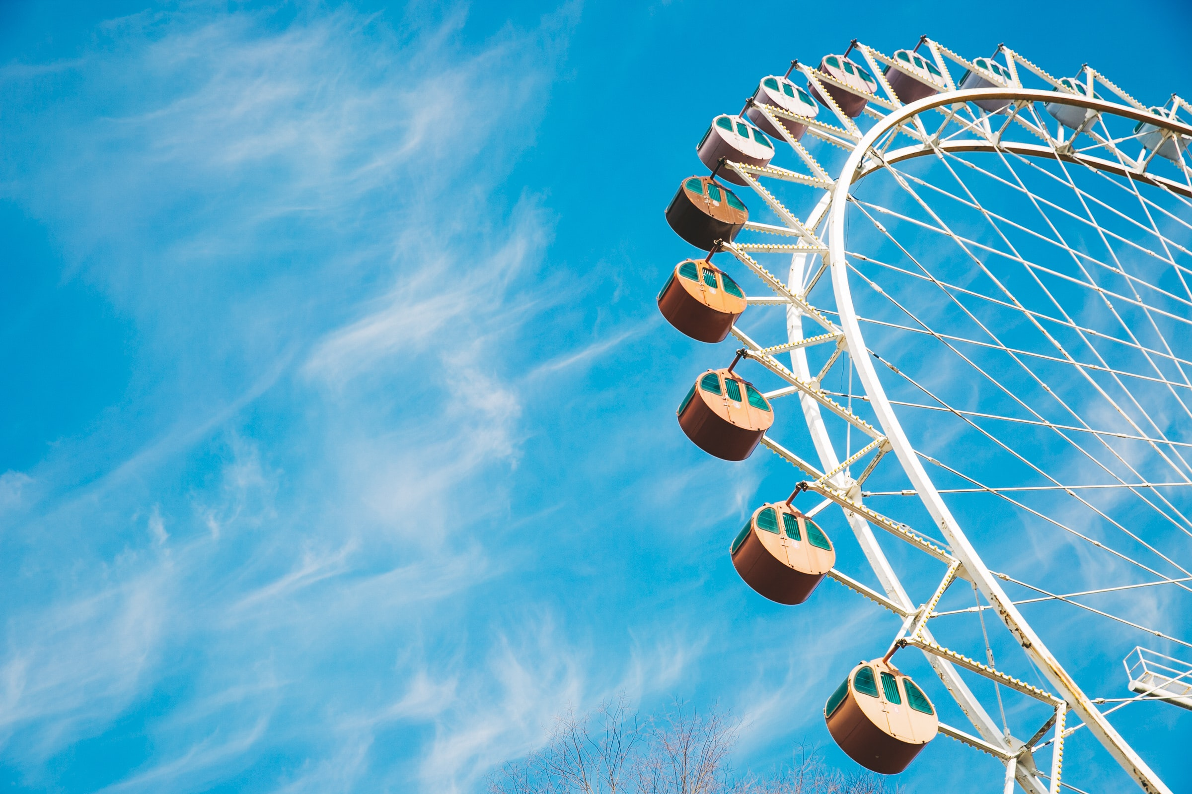 A Ferris wheel at a fairground against a blue sky