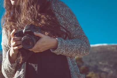 woman holding black canon dslr camera canon teams background