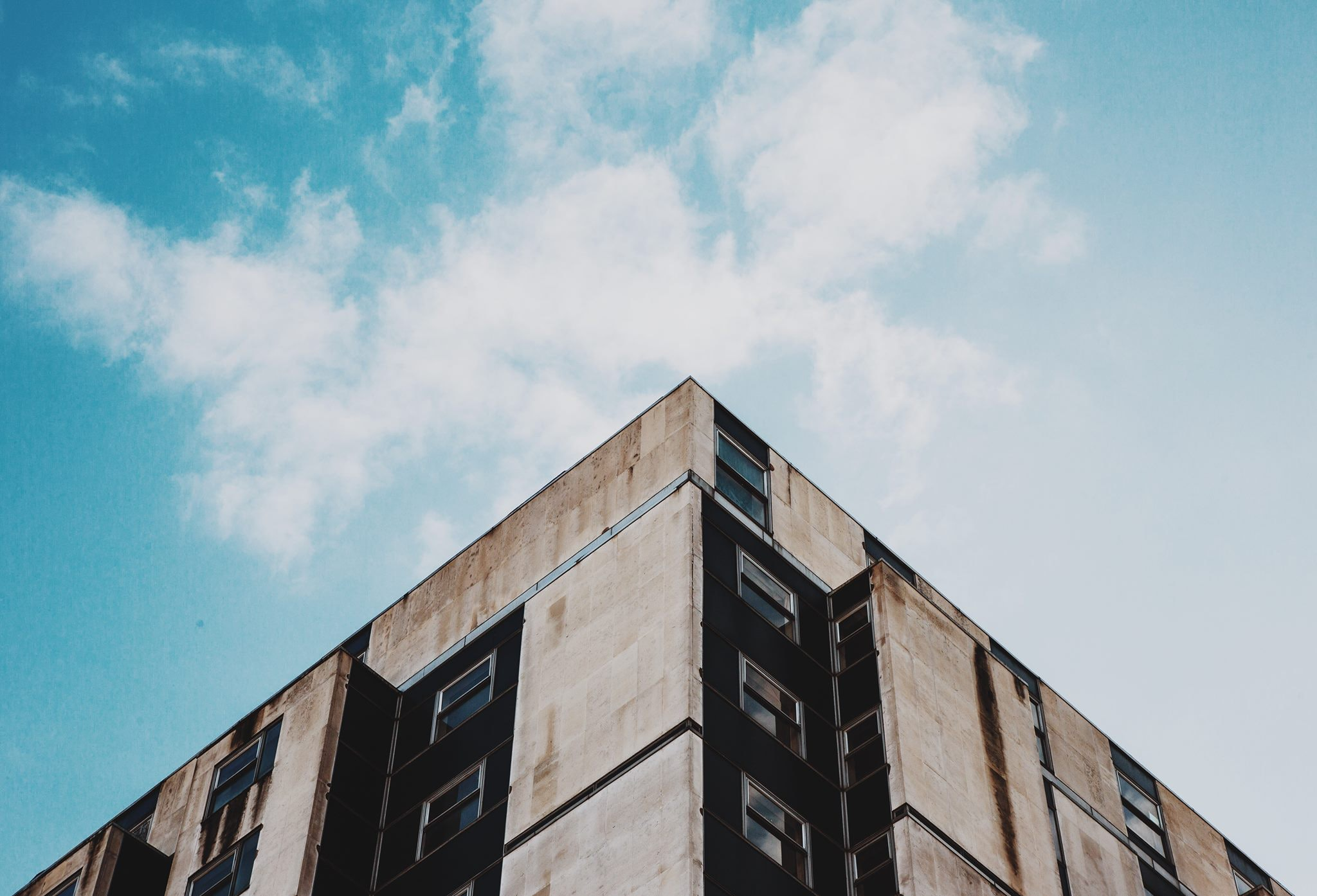 low-angle photography of beige and black concrete building under clear blue sky