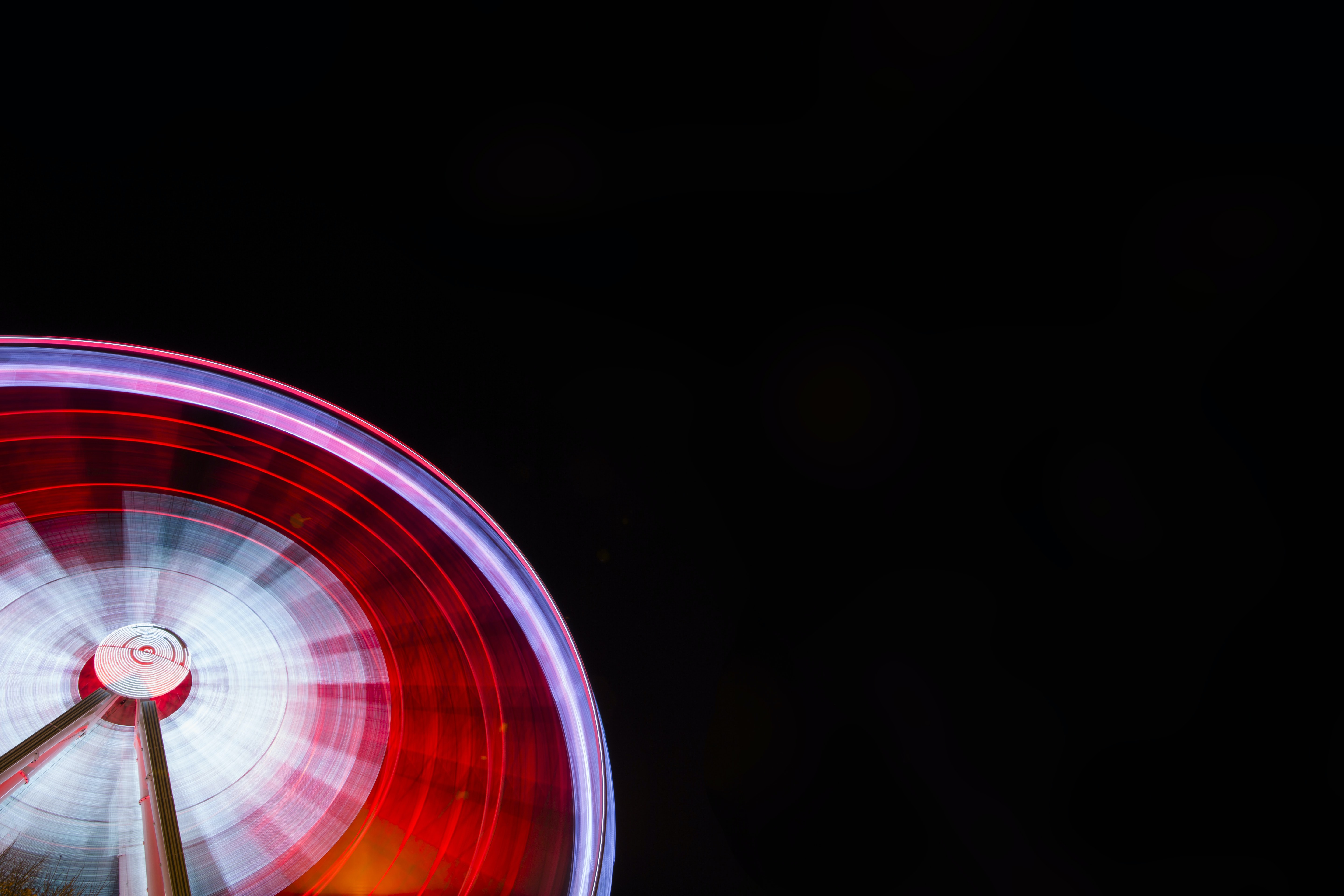 A partial image of a big red illuminated ferris wheel spinning at a fair
