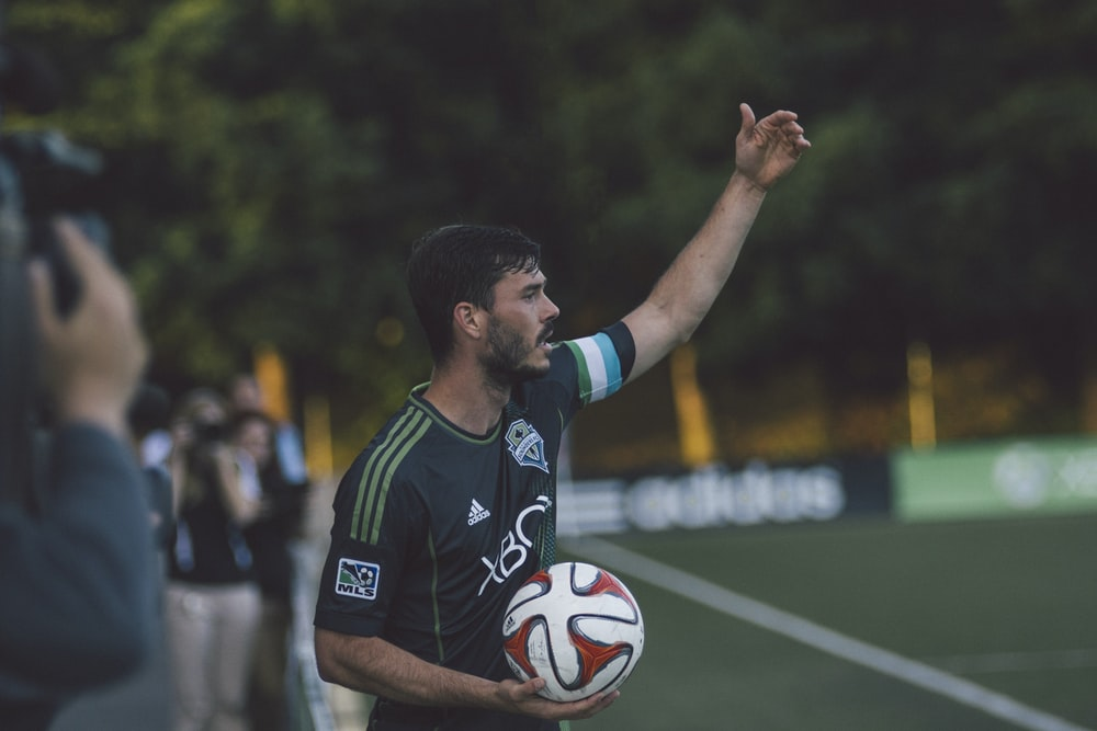 man in black and green Adidas jersey shirt holding soccer ball