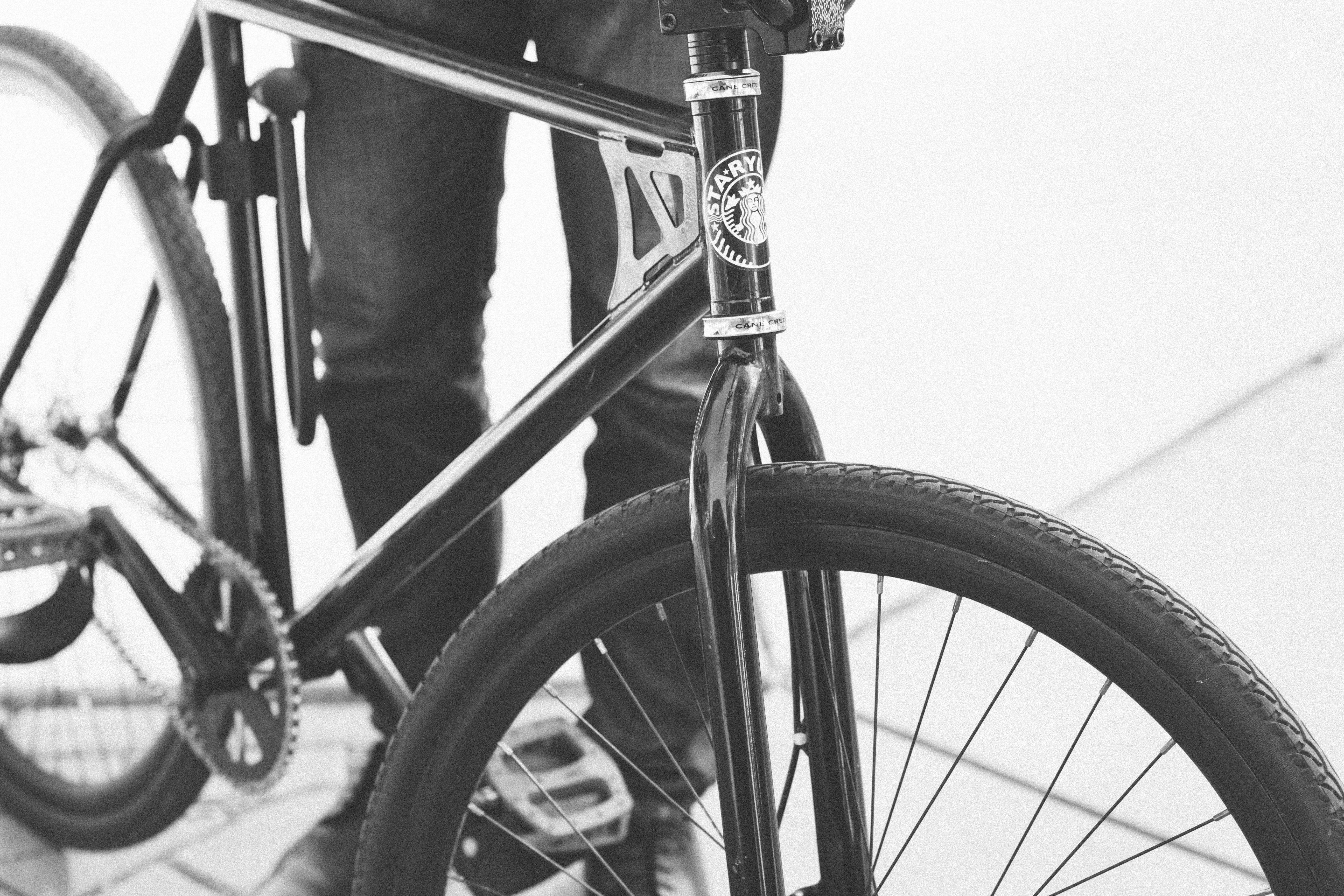 Black and white close up shot of bike and person's legs