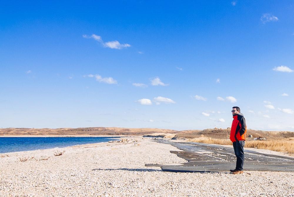 man in black jacket standing on brown sand under blue sky during daytime