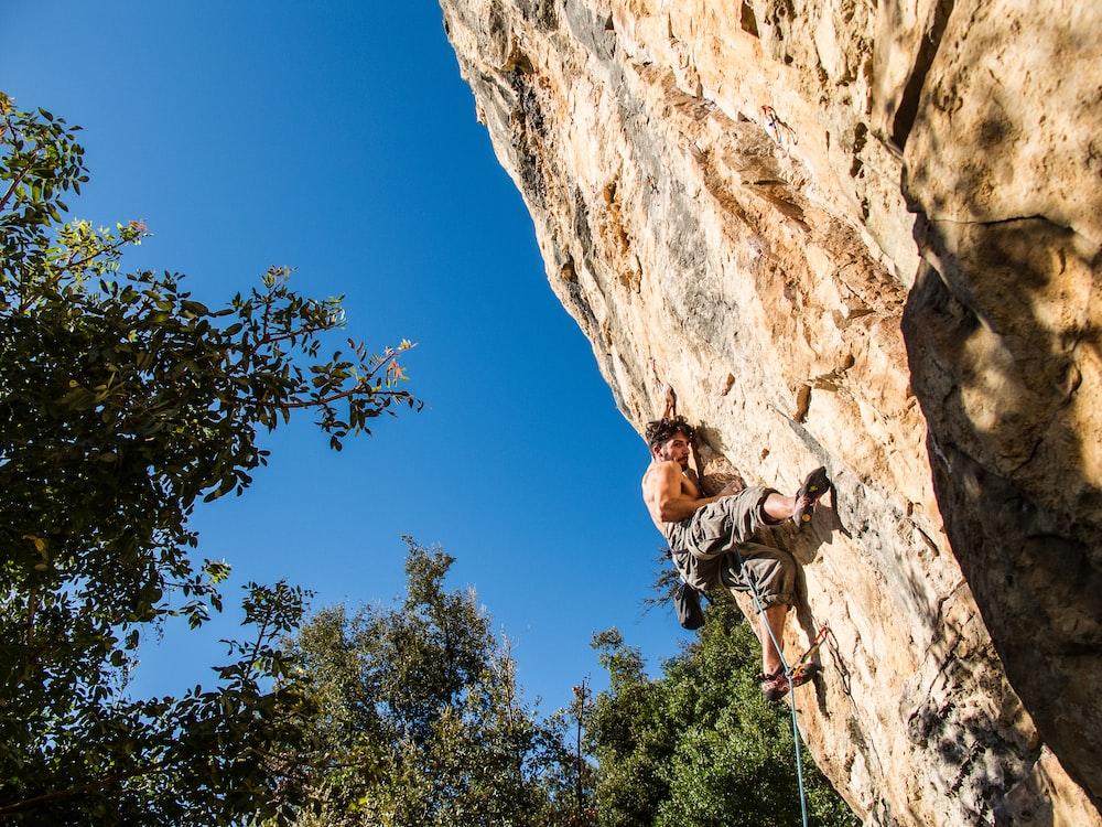 man climbing on mountain during daytime
