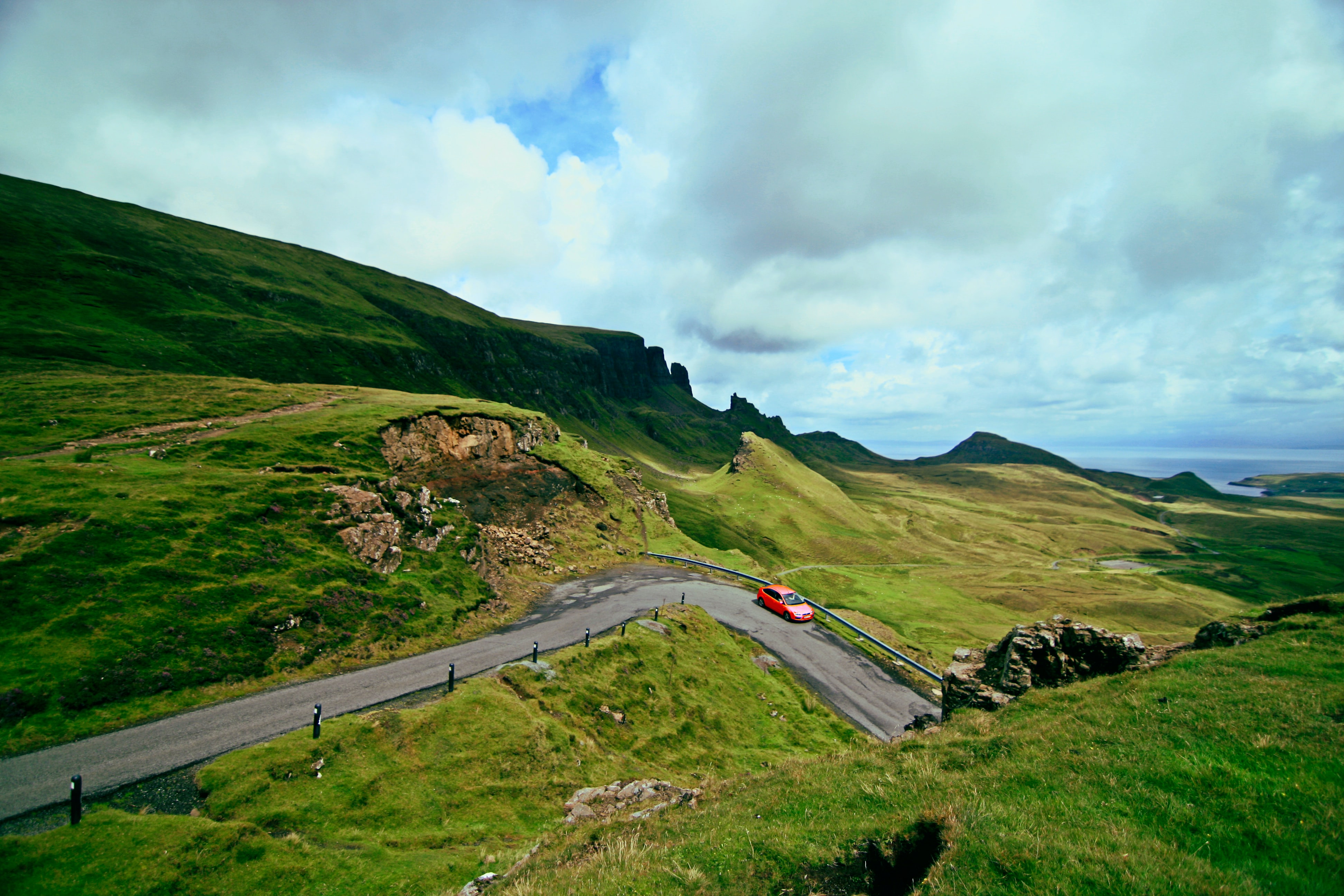Red car driving on countryside road surrounded by green landscape and sloped cliffs