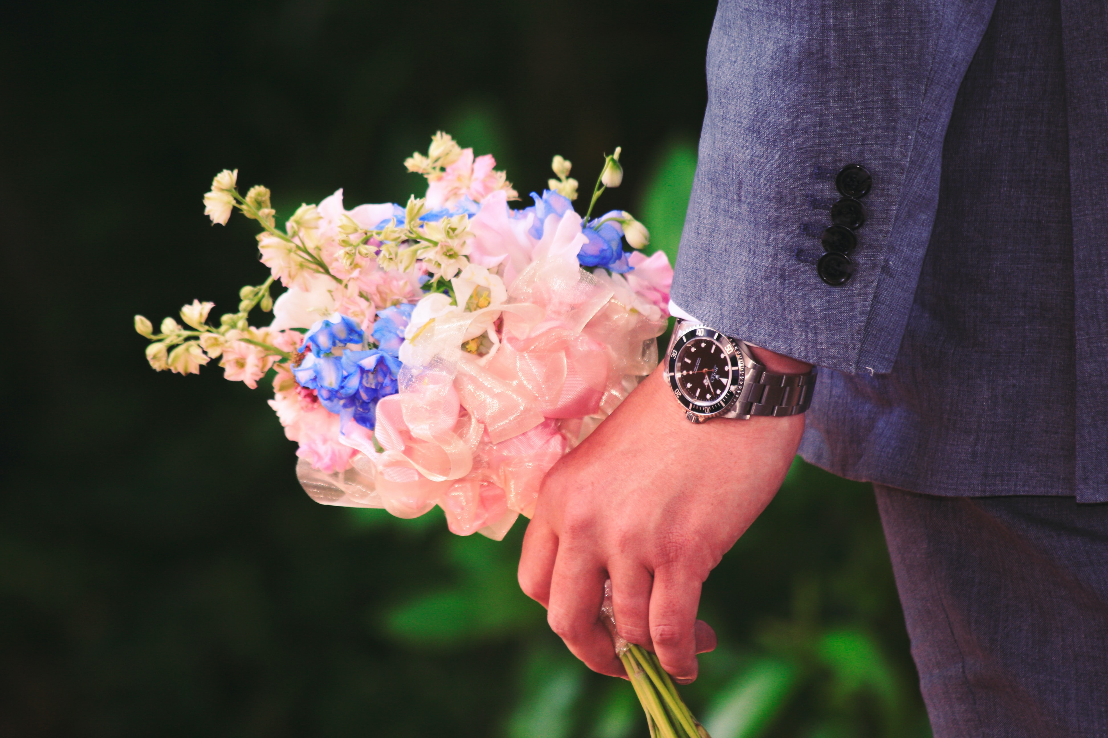 Man in tuxedo grips bouquet of pink, purple and white flowers