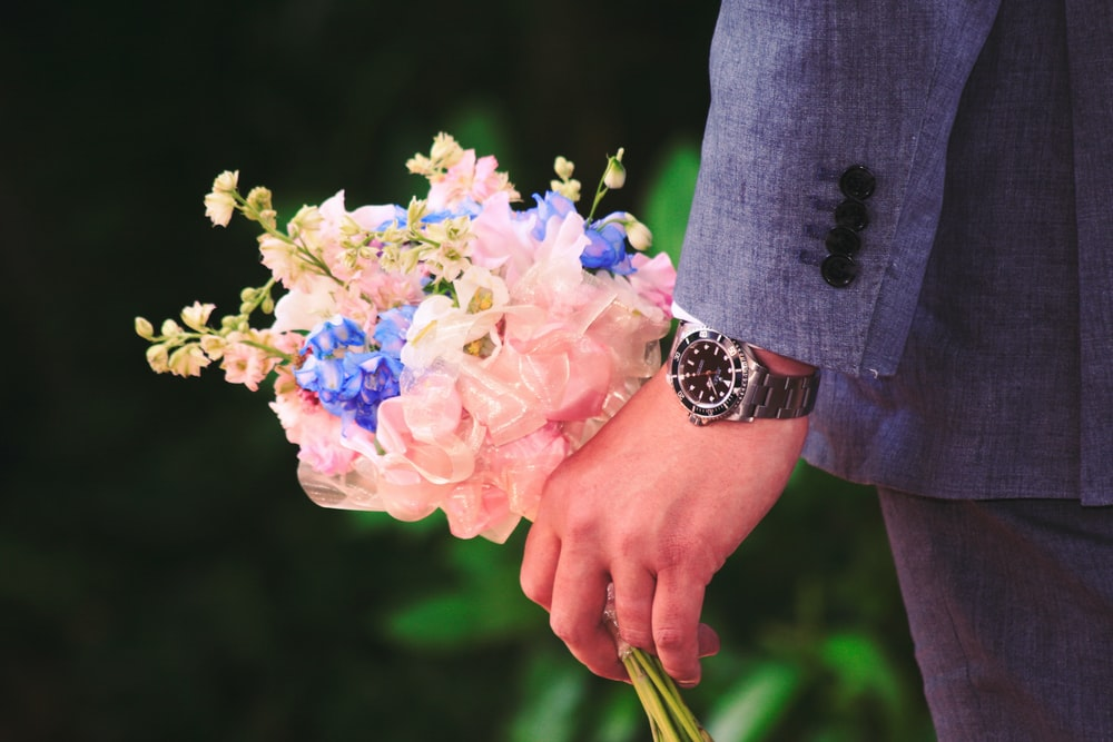 close up photography of man holding flowers