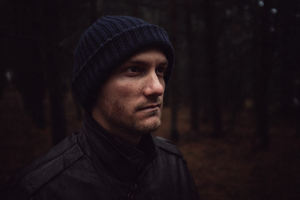 shallow focus of man standing on forest