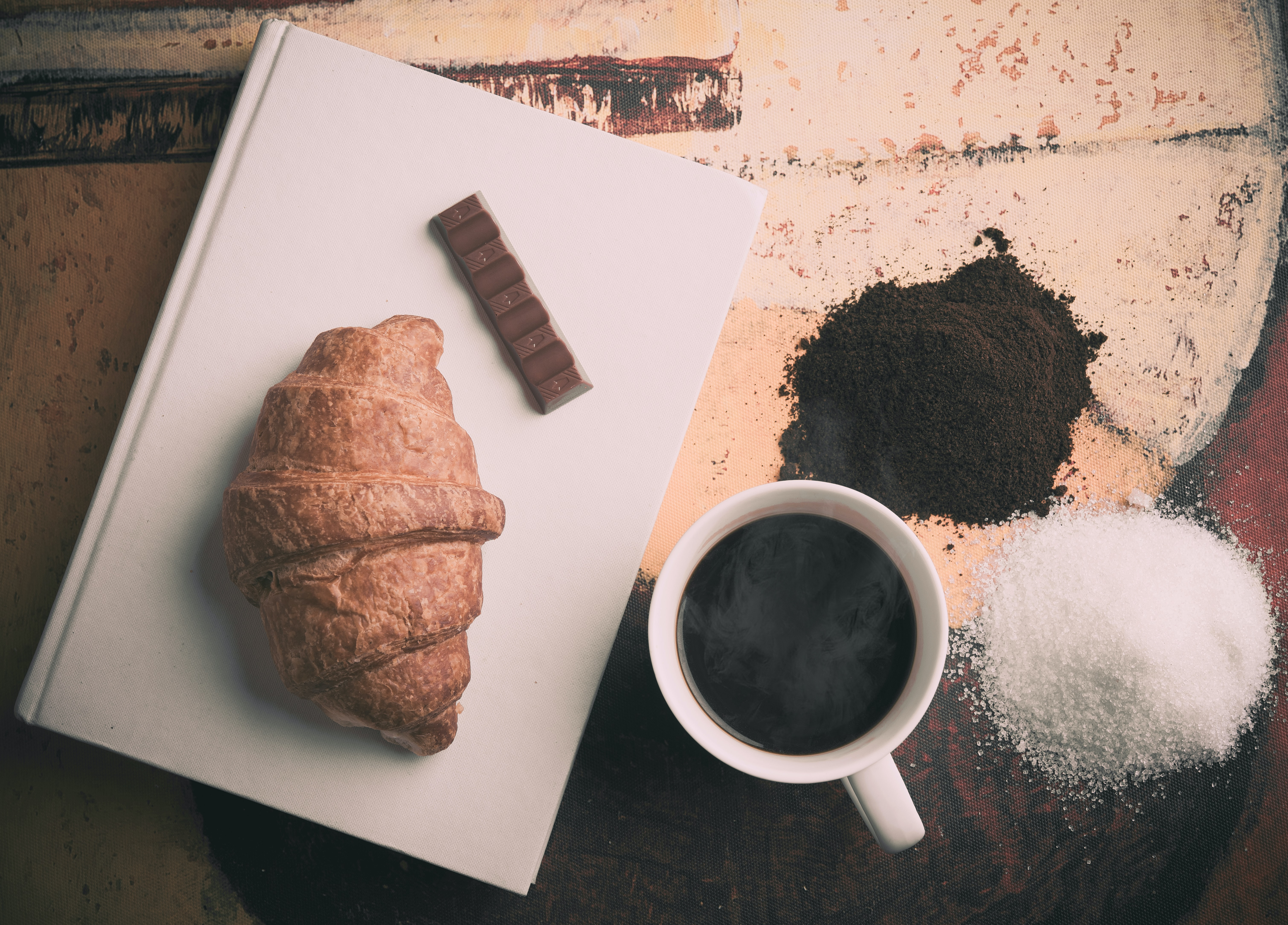 A croissant, chocolate, book, coffee cup, sugar, and coffee grounds on a table