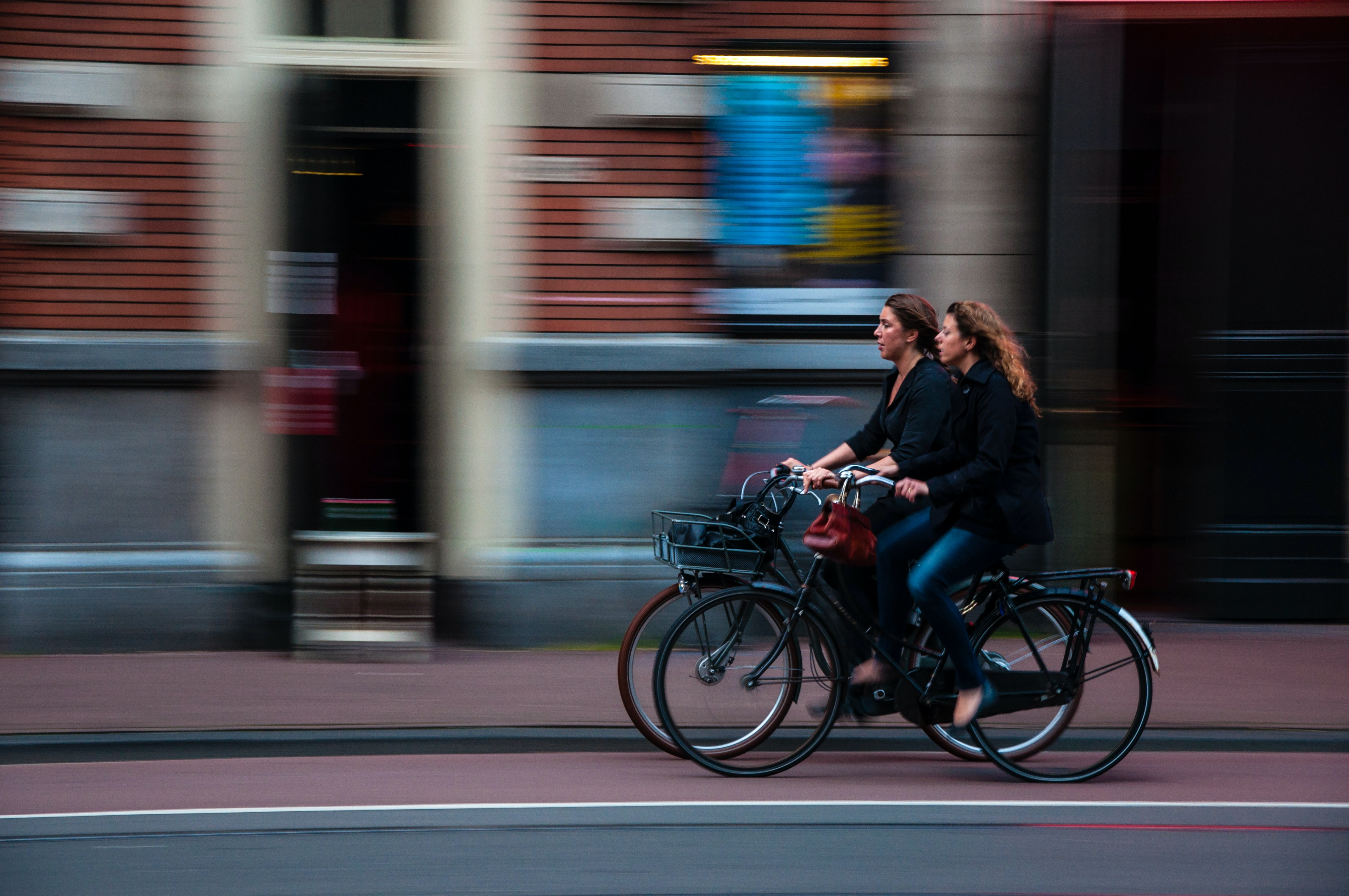 Two women riding their bicycles down the street in the bike lane