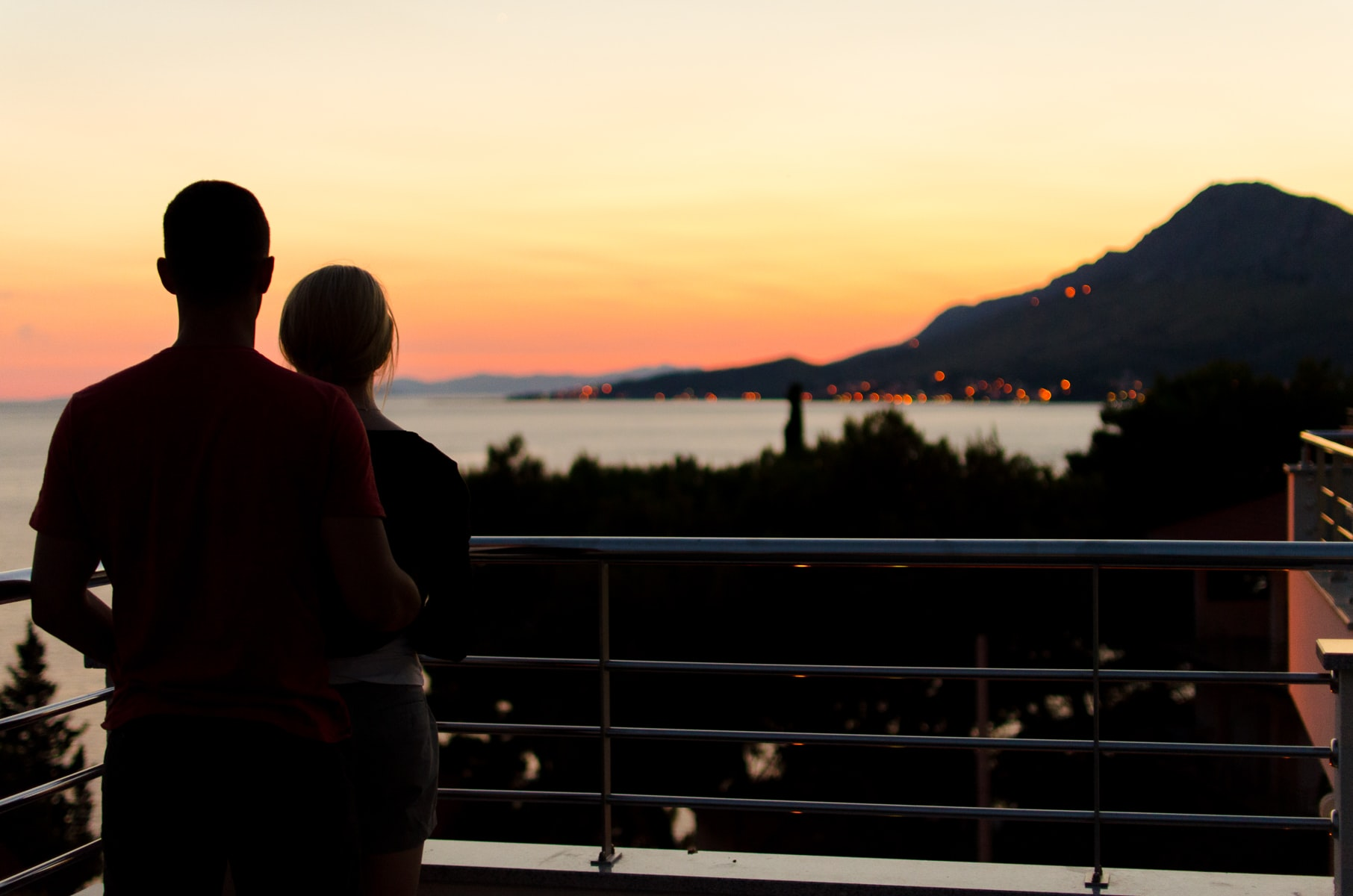 Silhouetted lovers look out over the ocean from a landing in the hills above