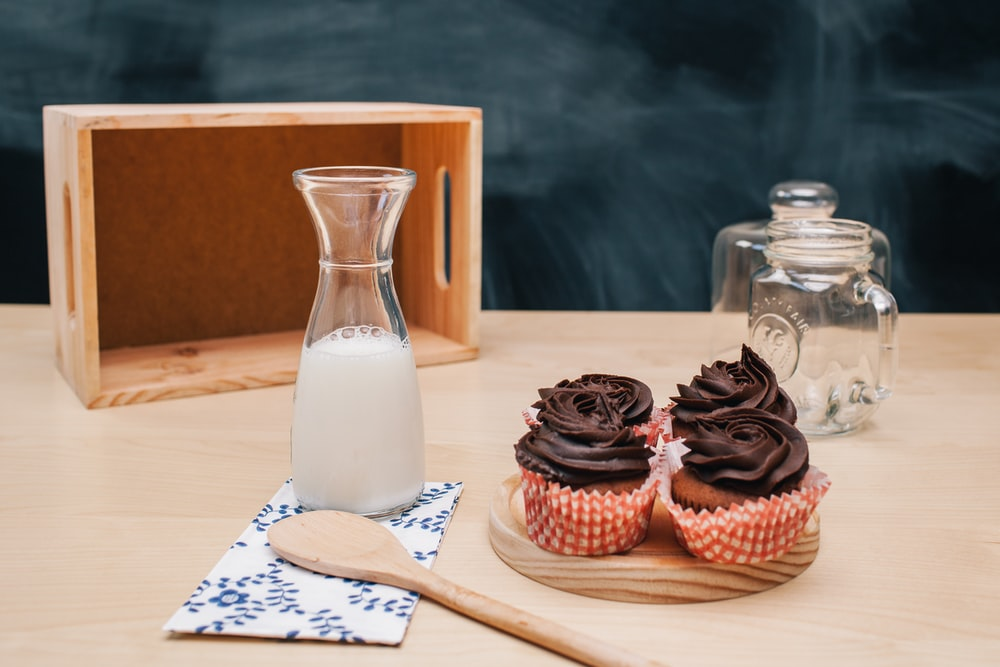 four cupcakes on brown coaster and milk jar