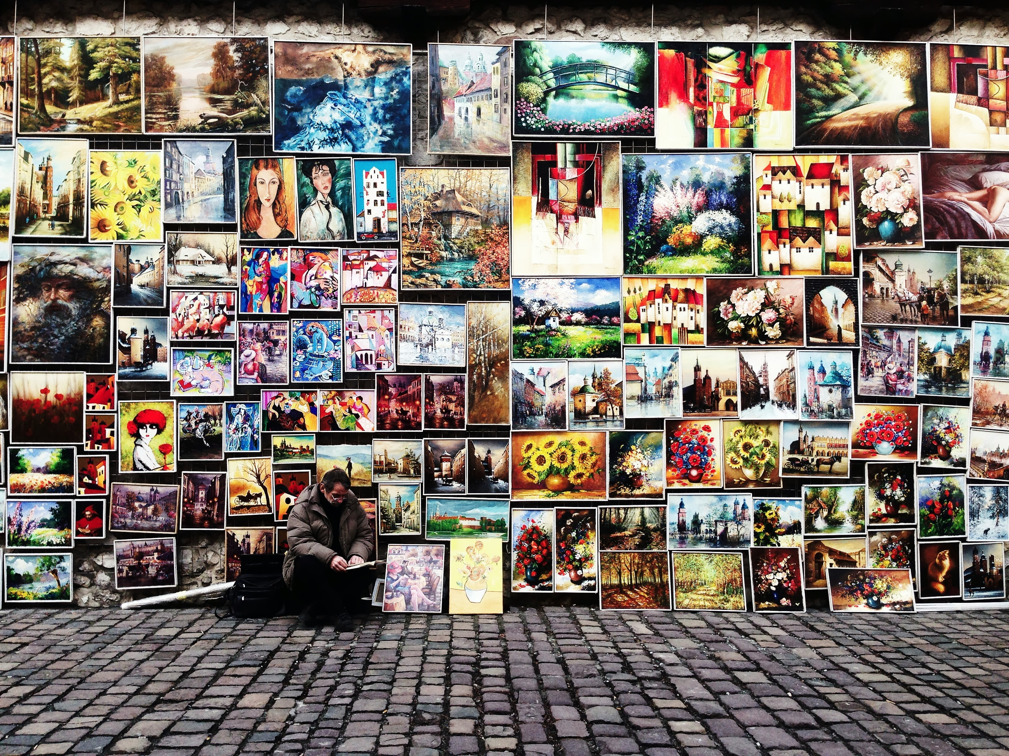 Street artist sitting in front of wall of diverse, colorful paintings that make beautiful pattern