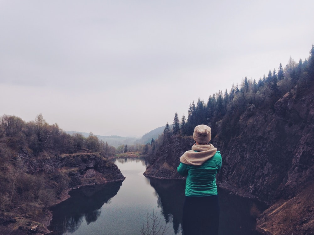person staring at body of water