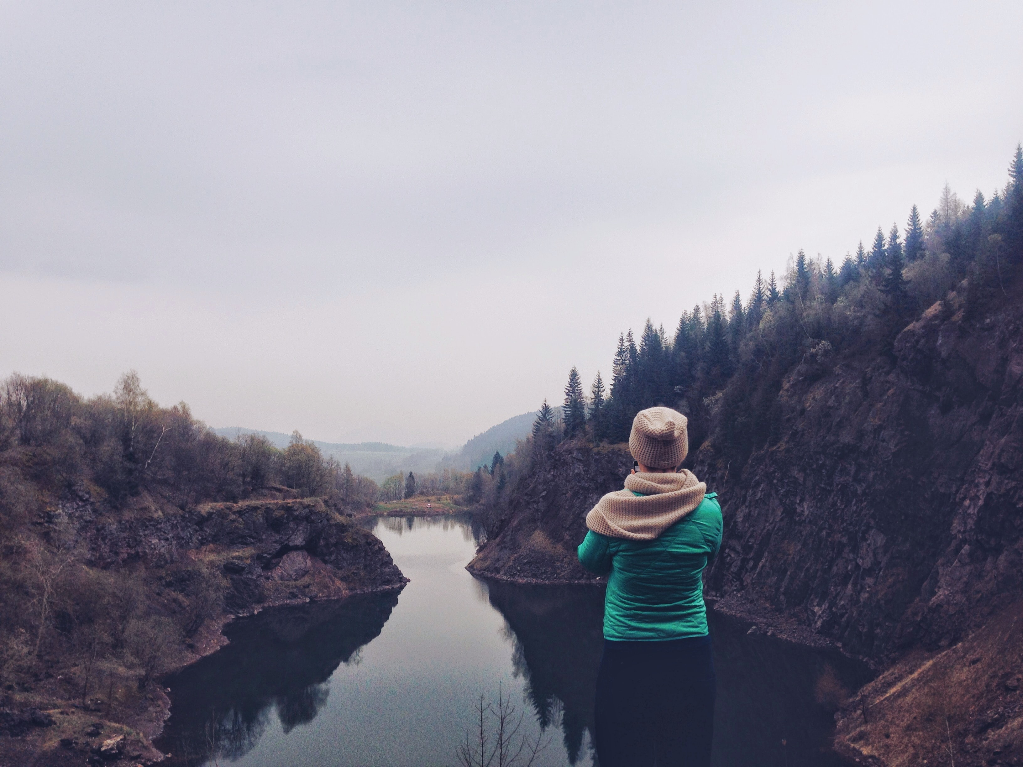 A woman admiring a small lake in a rocky basin on a cloudy day