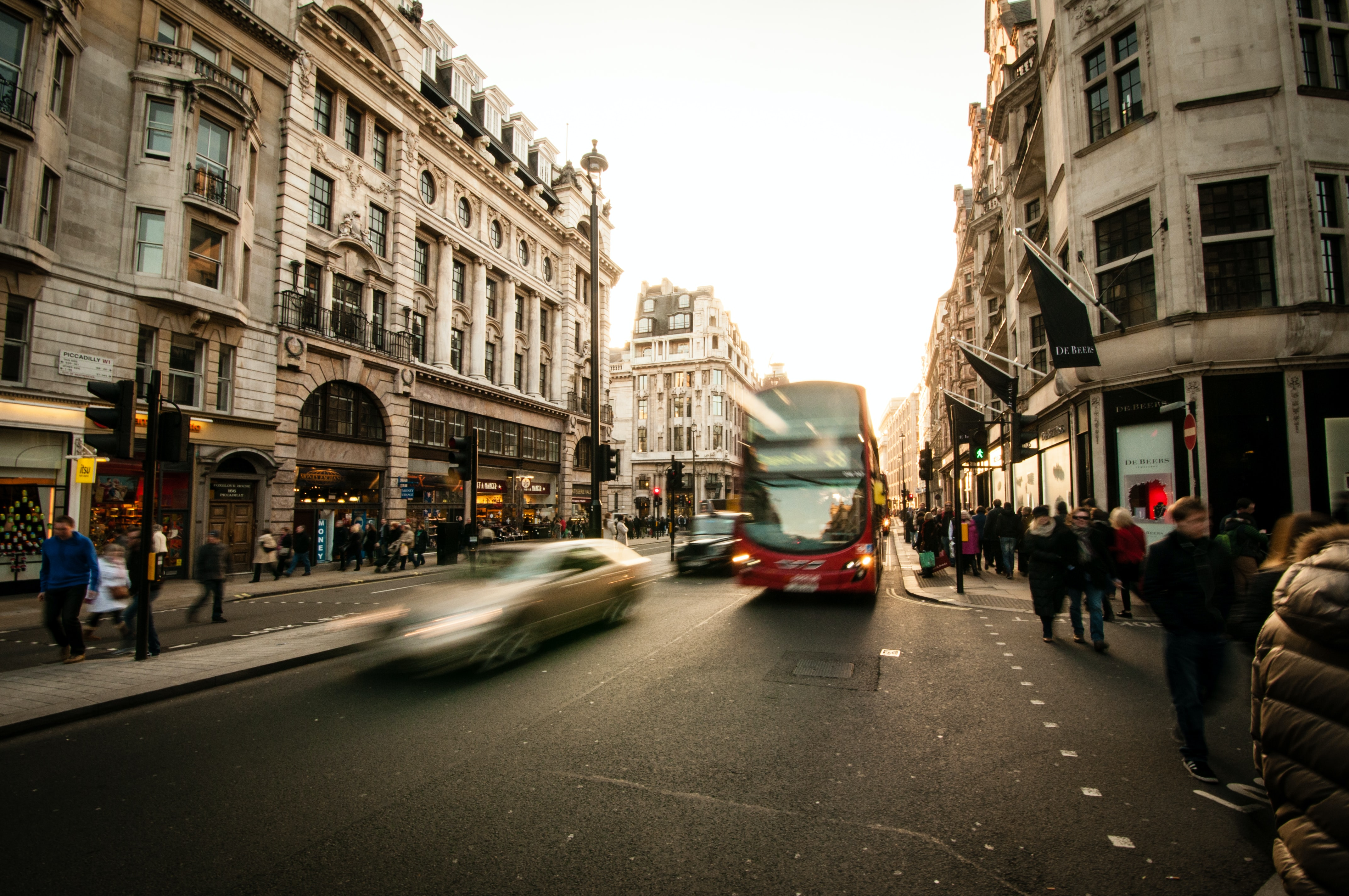 Time lapse shot of busy London street, silver car, red double decker bus pedestrians on sidewalk