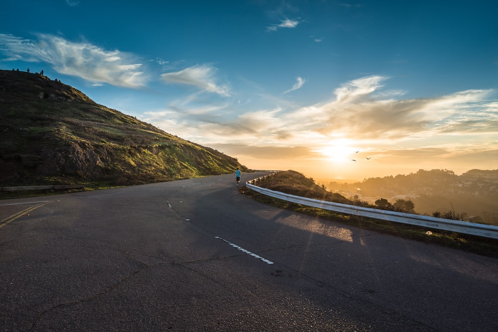 person running on road street cliff during golden hour