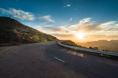 person running on road street cliff during golden hour inspirational teams background
