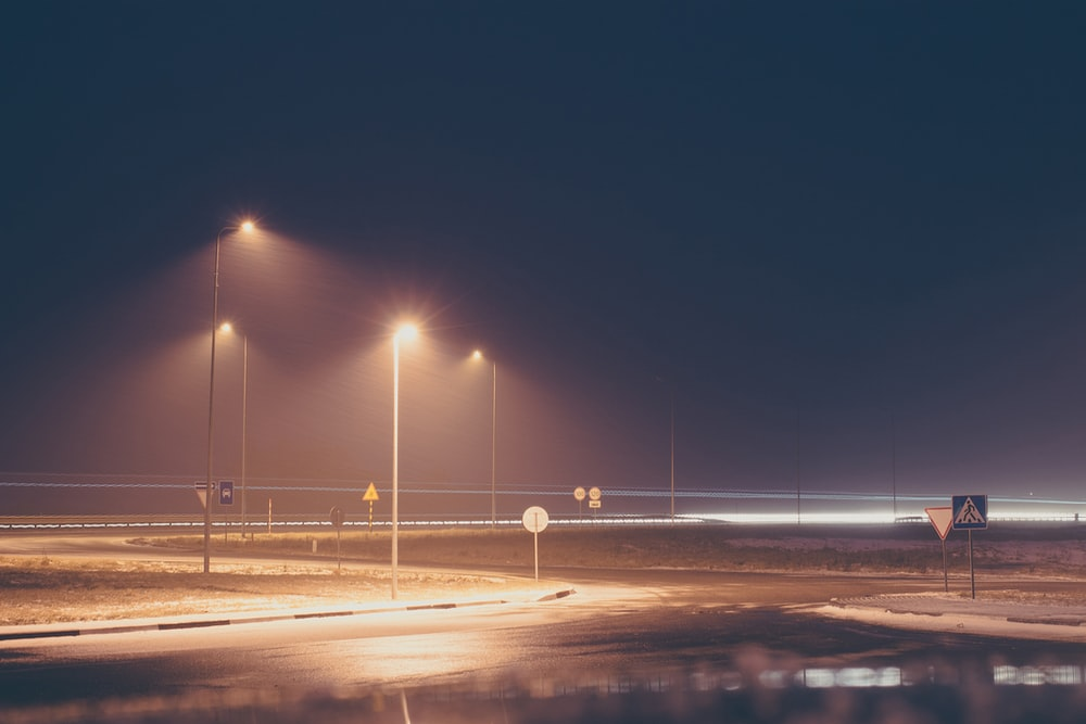 concrete road with turned on post lamp lights at nighttime