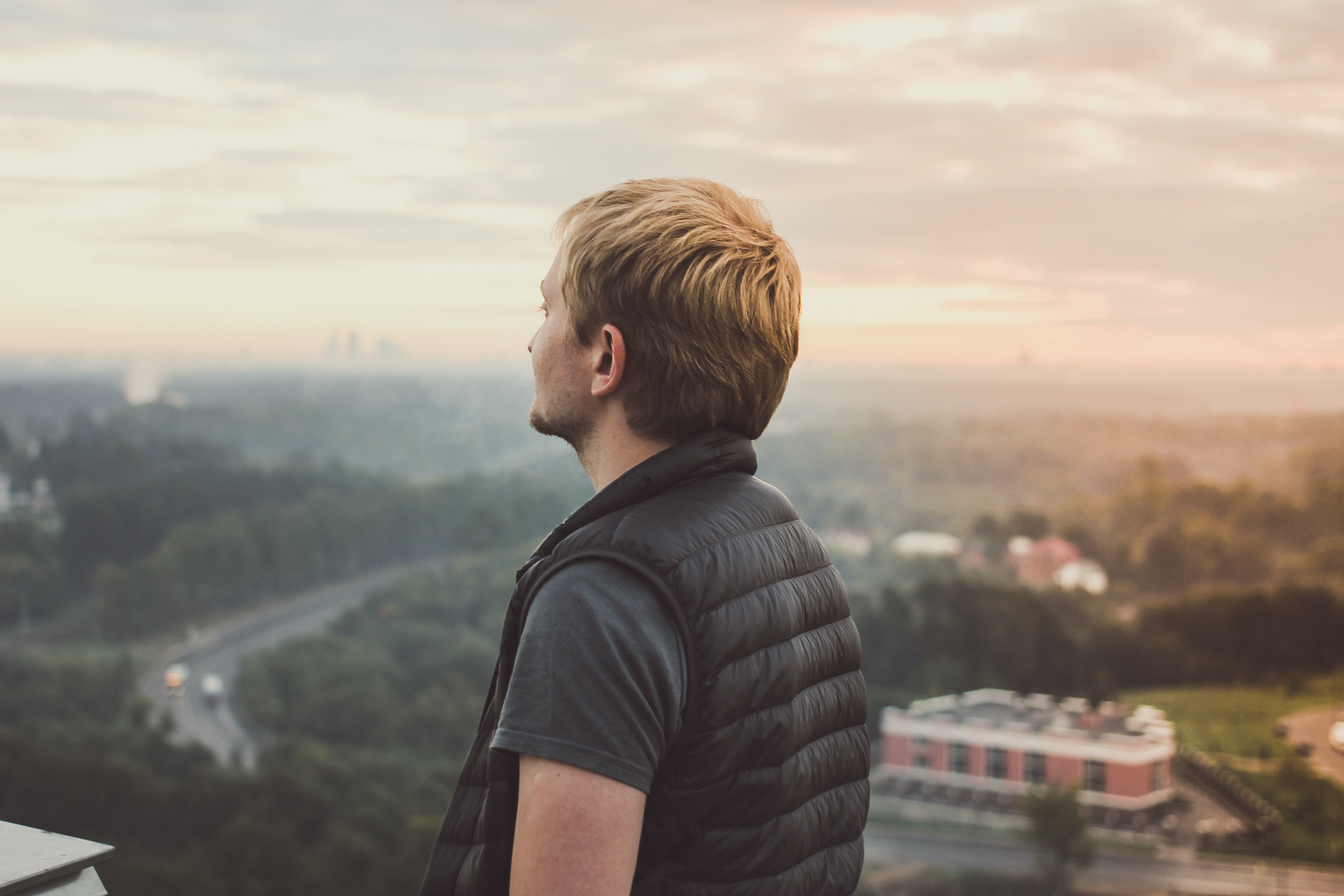 A man in a vest looking into the distance over a landscape of trees and buildings