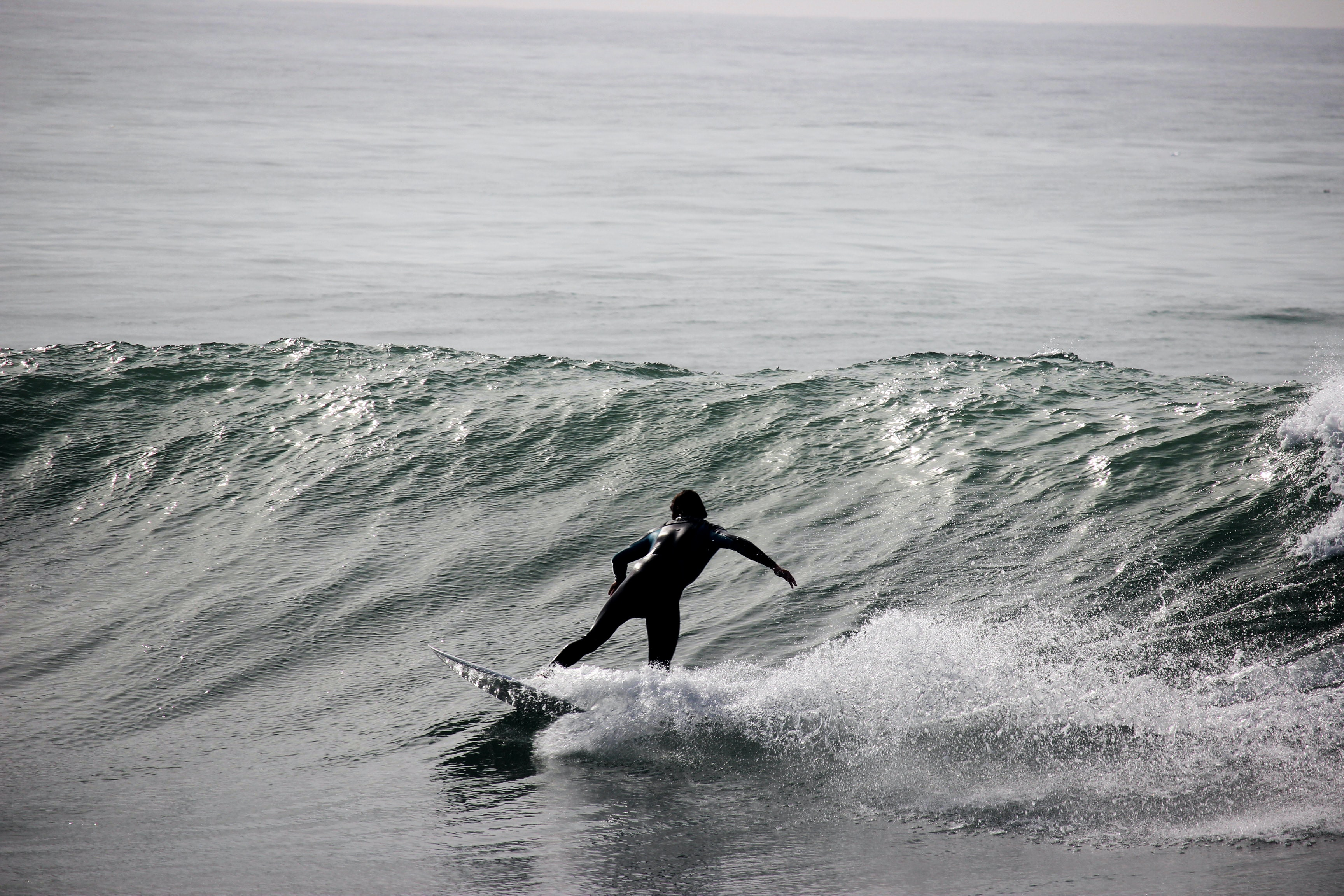 grayscale photography of surfer on body of water during daytime