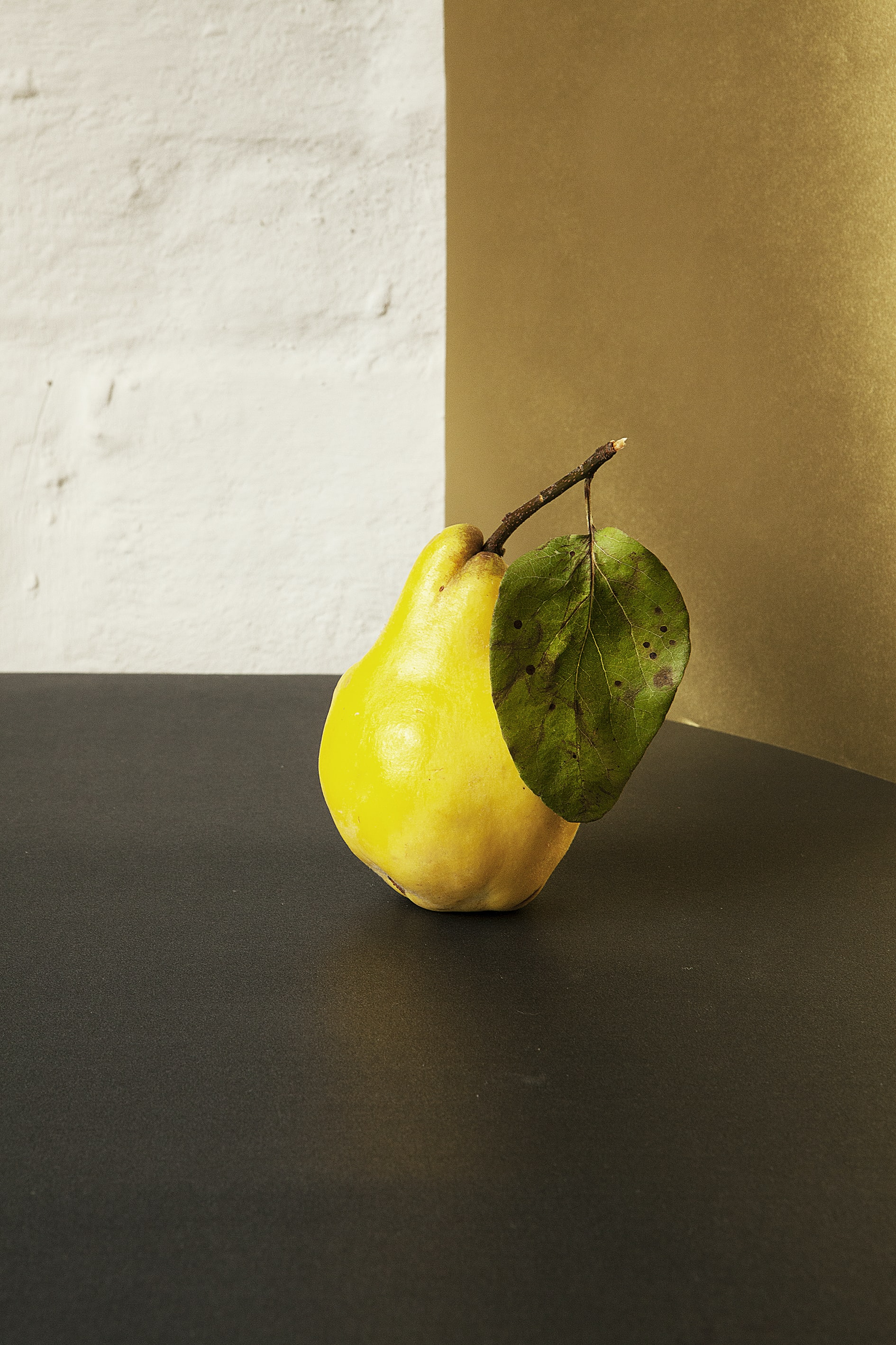 Freshly picked juicy yellow pear with a leaf on a table