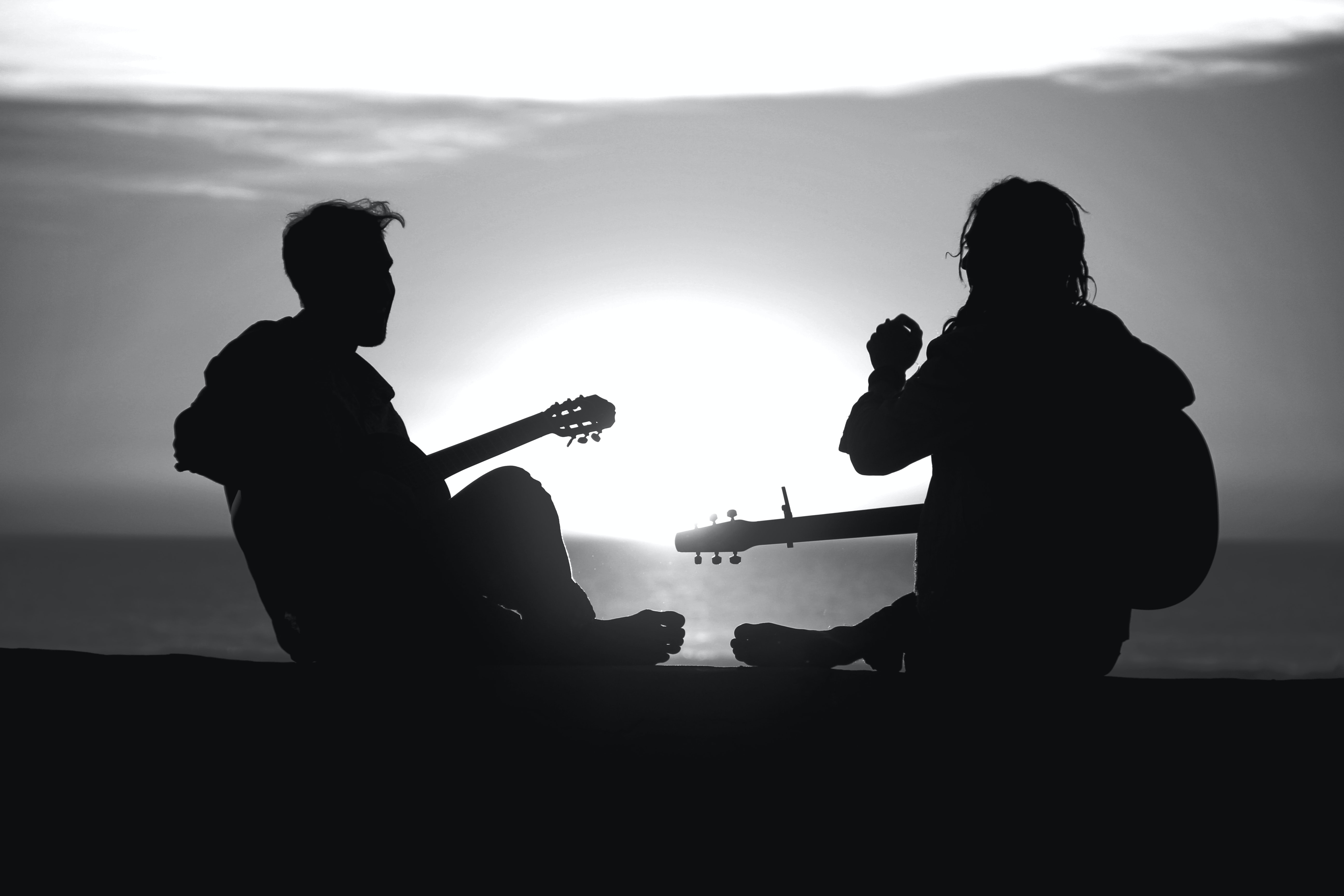 Two figures silhouetted against the sun, laughing with musical instruments