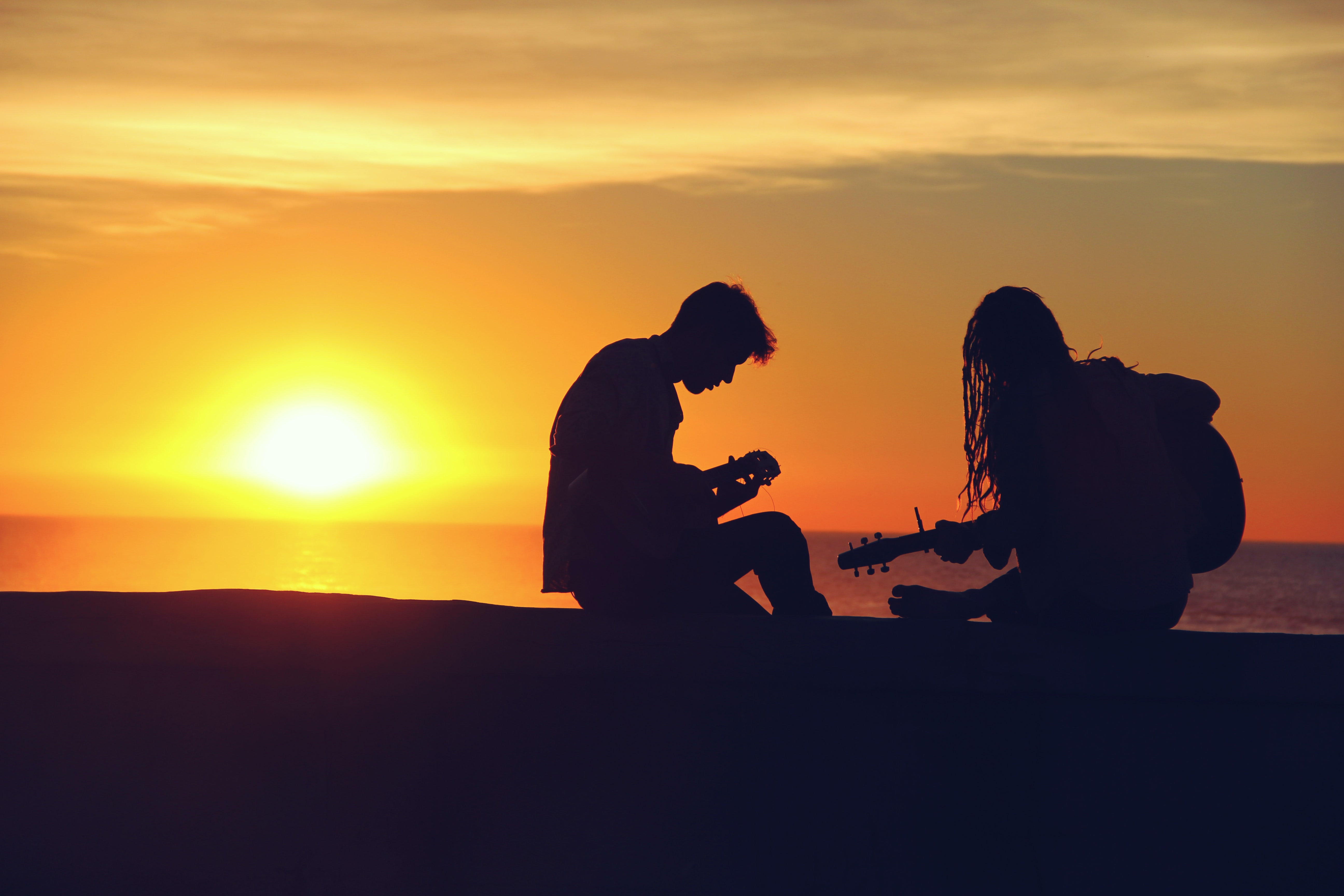 The silhouettes of a boy and a girl with guitars at the seaside against a setting sun