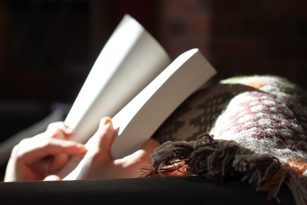 A person reading a book under a blanket