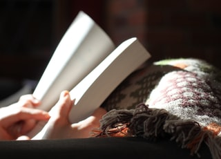 photo of person holding book near textile
