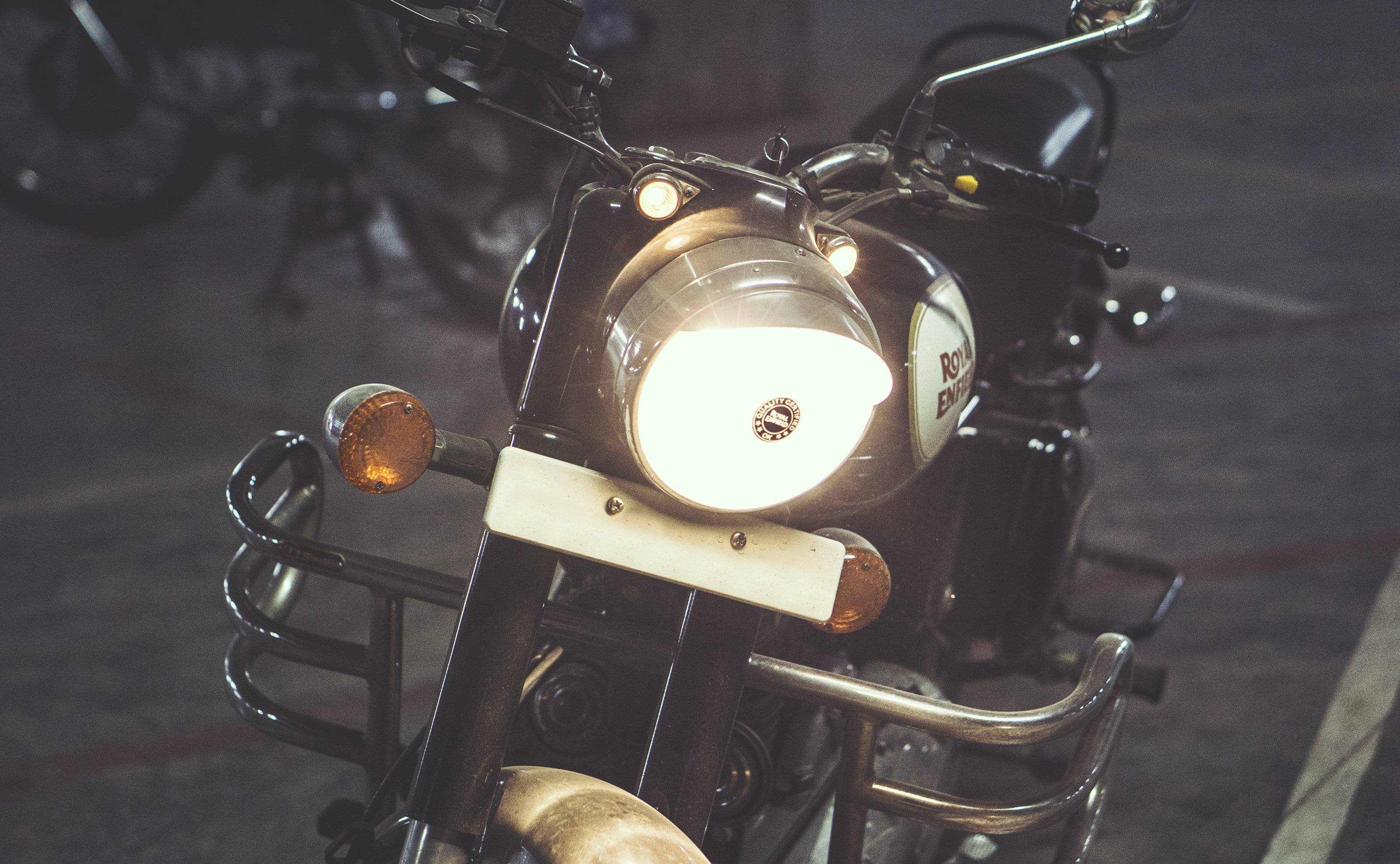 A motorcycle with its headlight on parked
