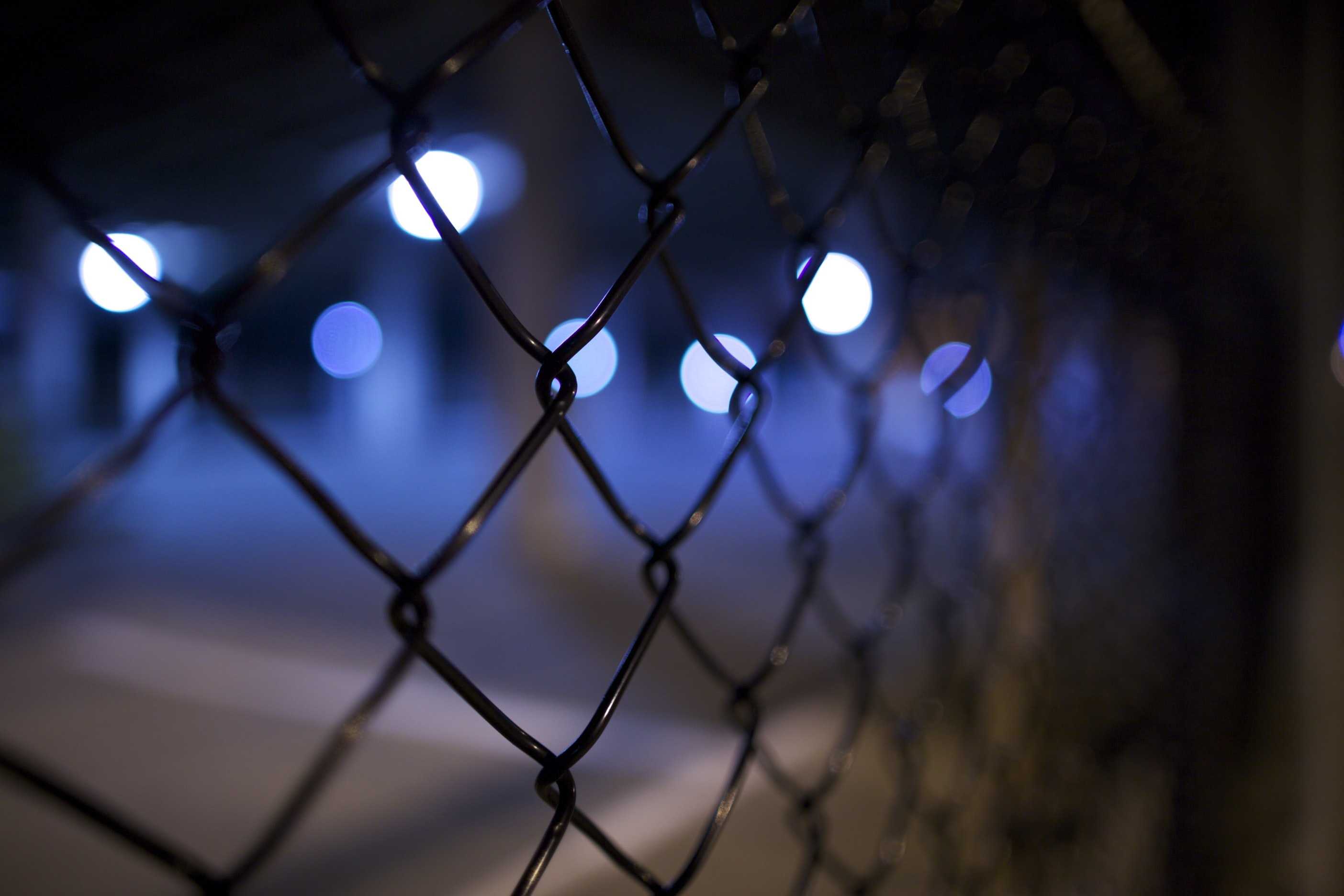 A chain link fence blocking several dots of blue and white light