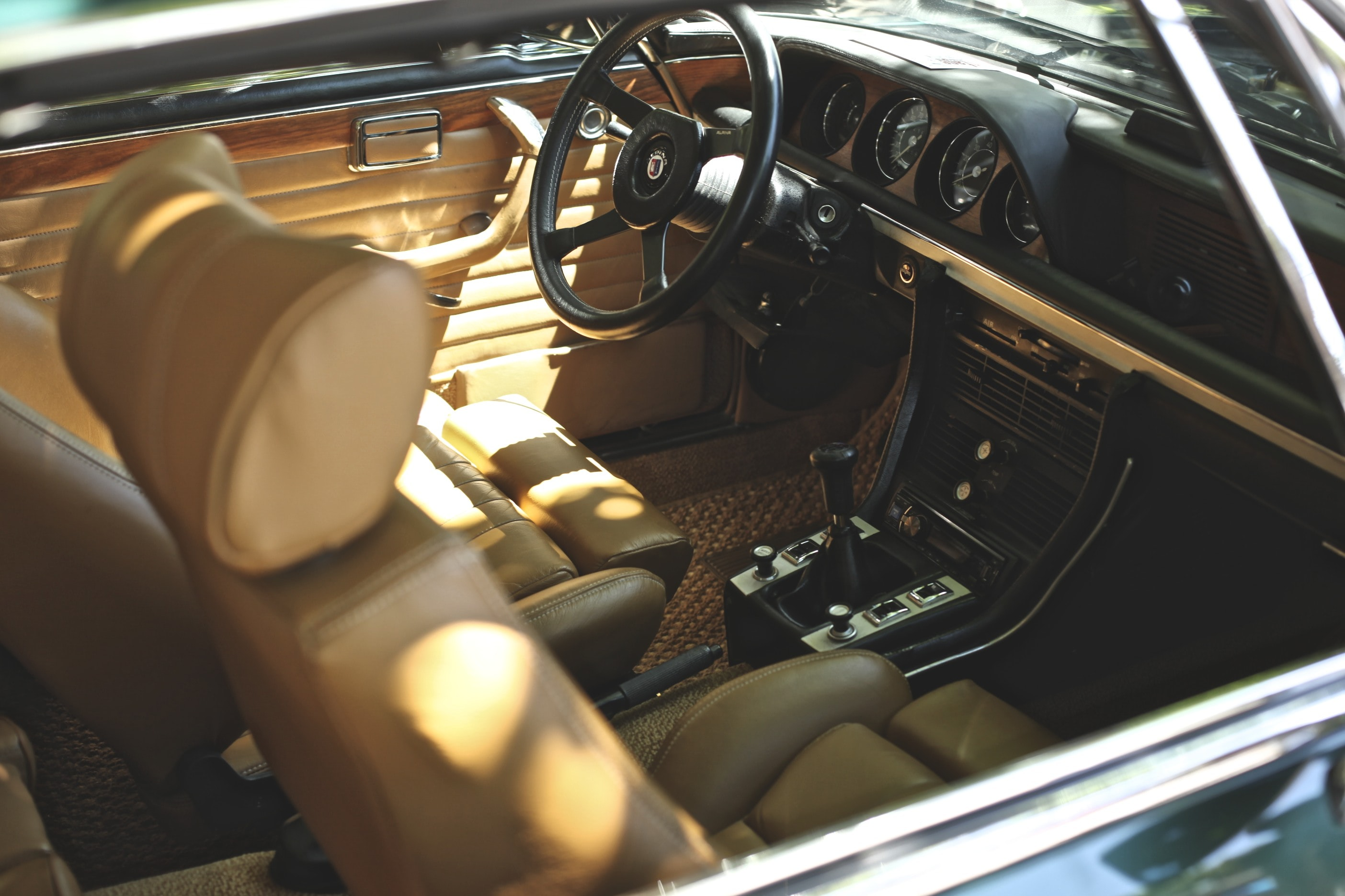 Interior shot of a vintage car with sunlight seeping in.