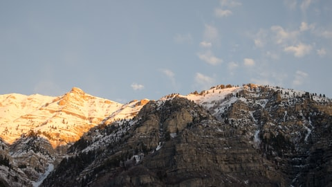 A rocky, snow-topped mountain in sunset