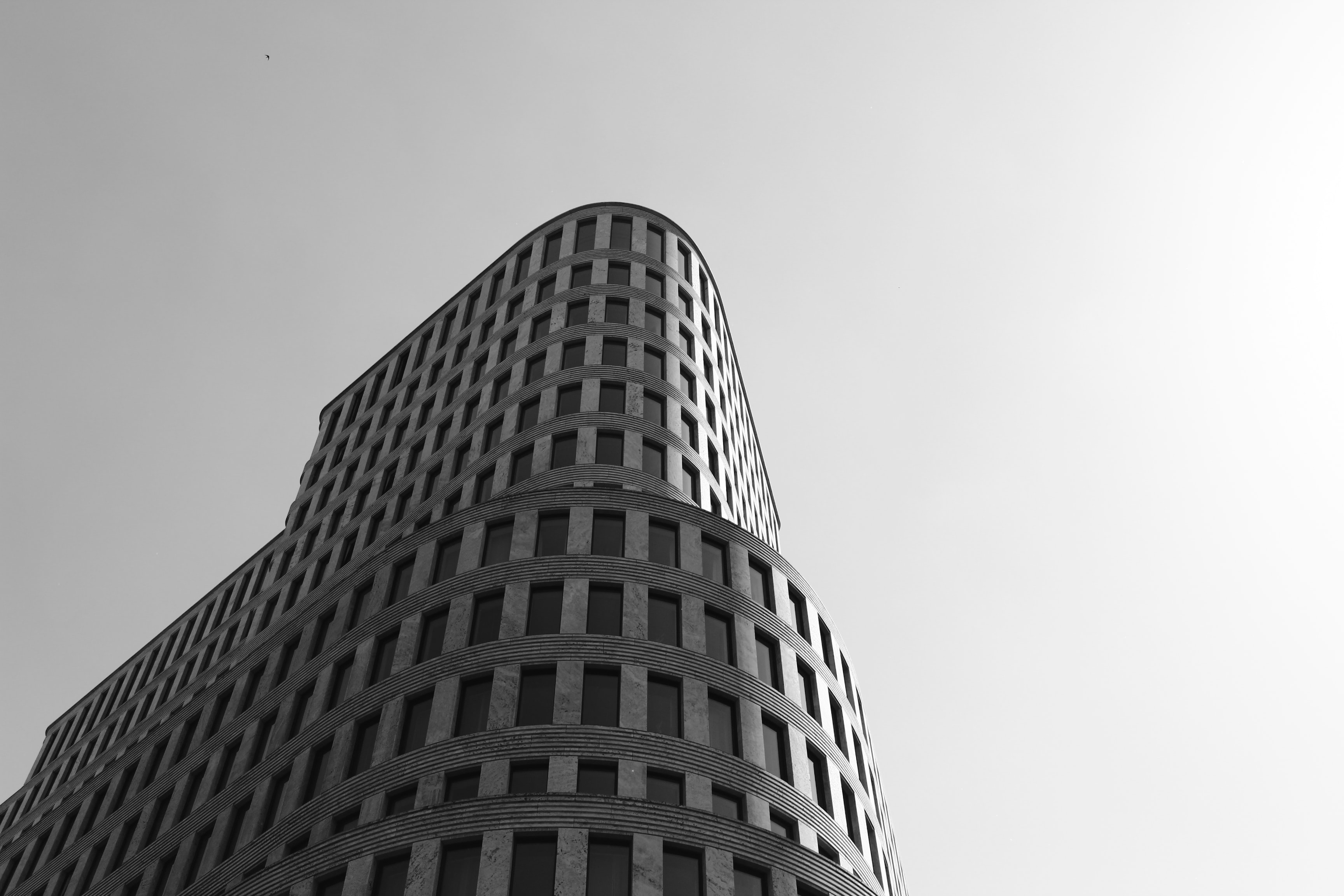 grayscale photo of concrete high-rise building under skies
