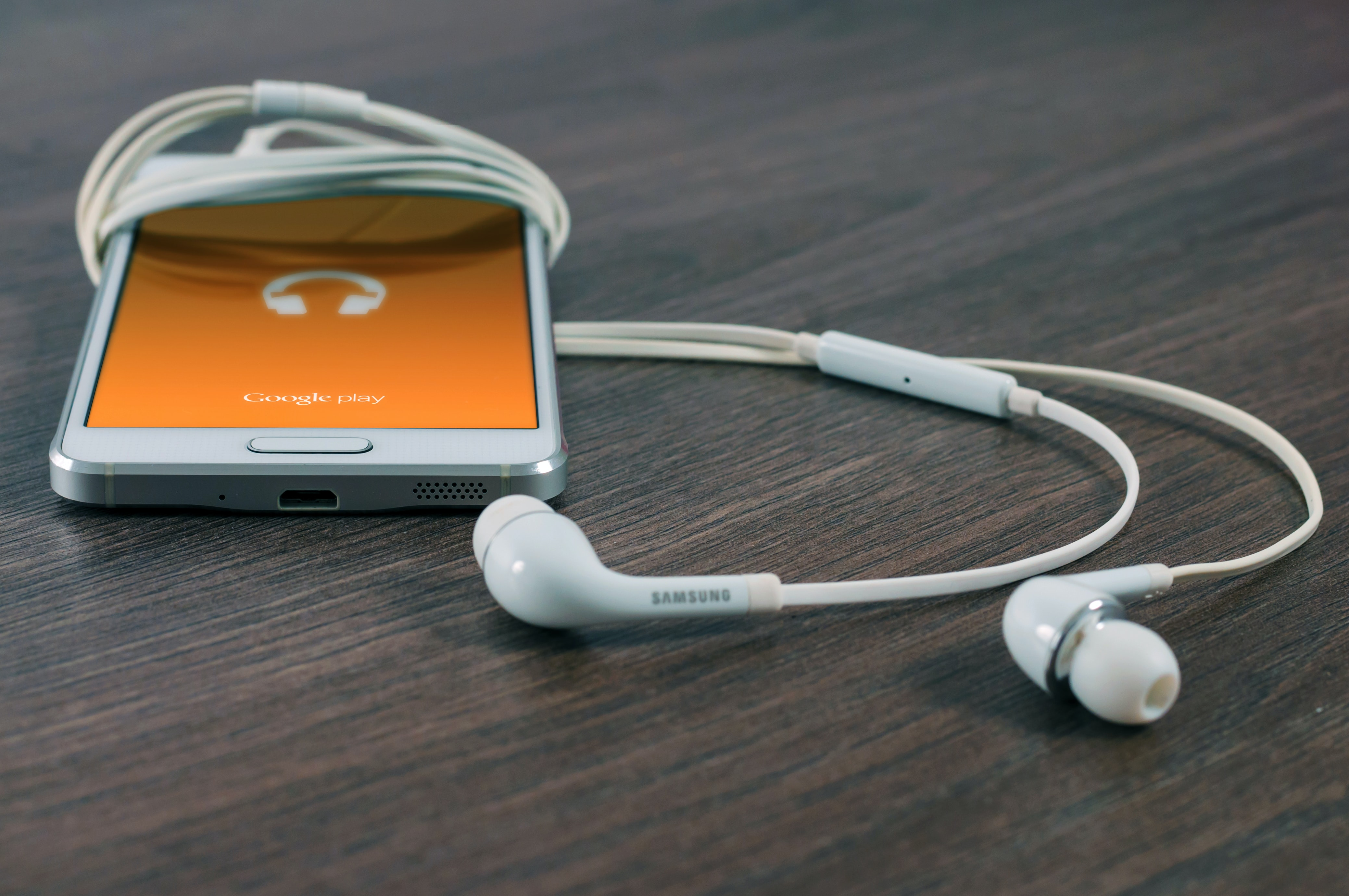Google Play music app on a smartphone with earphones on a wooden surface