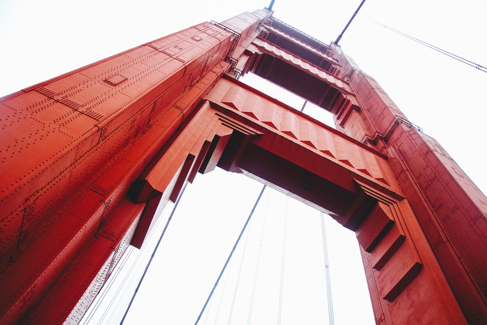 low angle photo of red suspension bridge