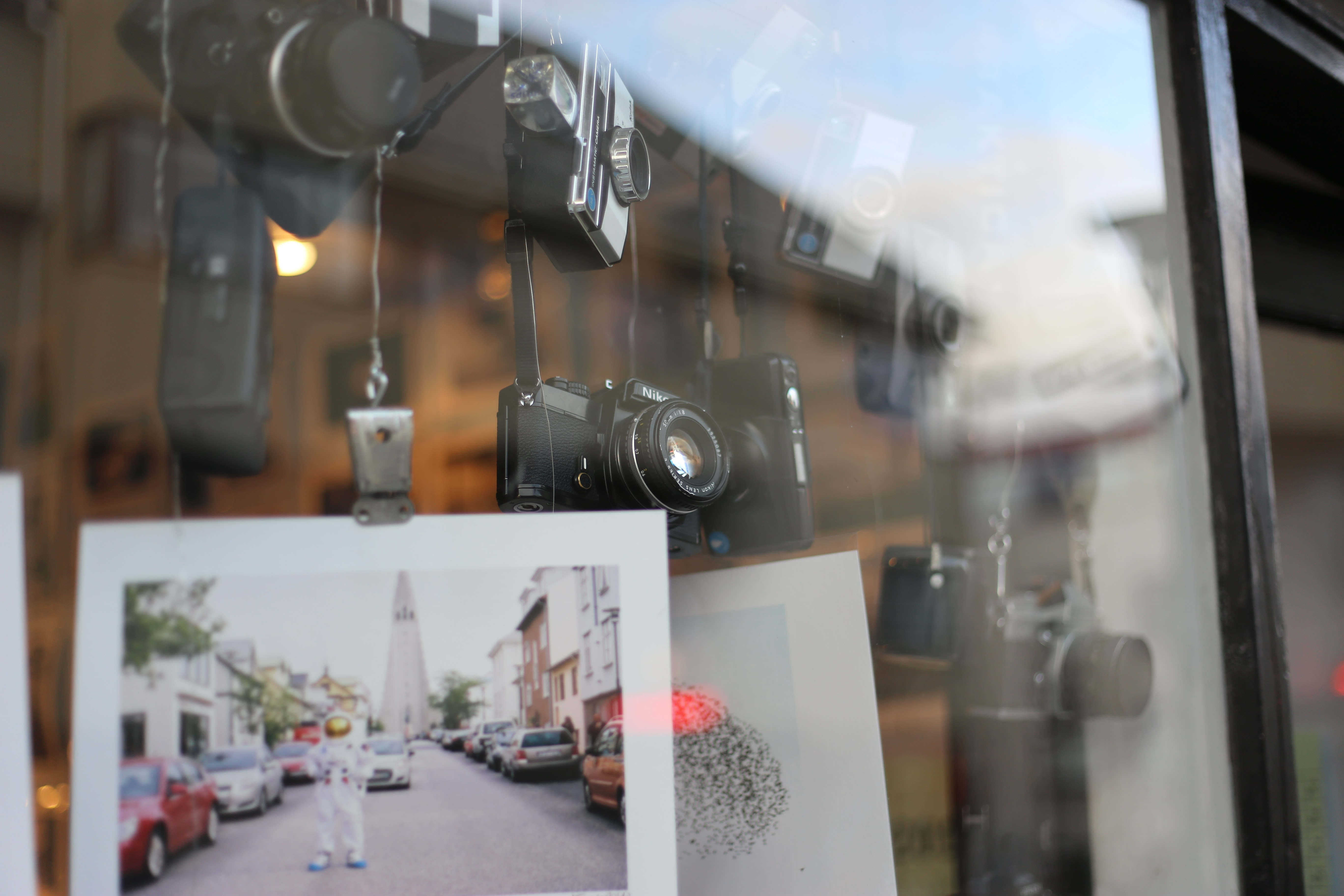 Vintage cameras and pictures hanging in window display with reflection