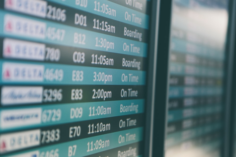 Airport departures timetable showing Delta and Alaska Airlines flights on time and boarding
