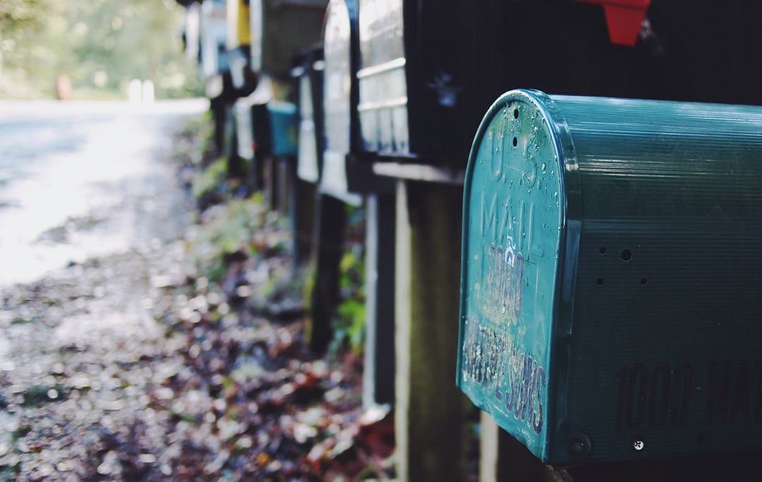 Multiple multicolored mailboxes placed alongside a muddy street strewn with leaves
