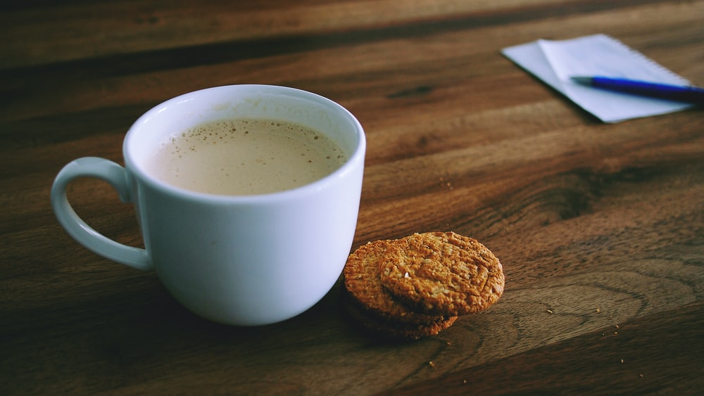shallow focus photography of white ceramic mug beside two baked cookies on brown wooden board