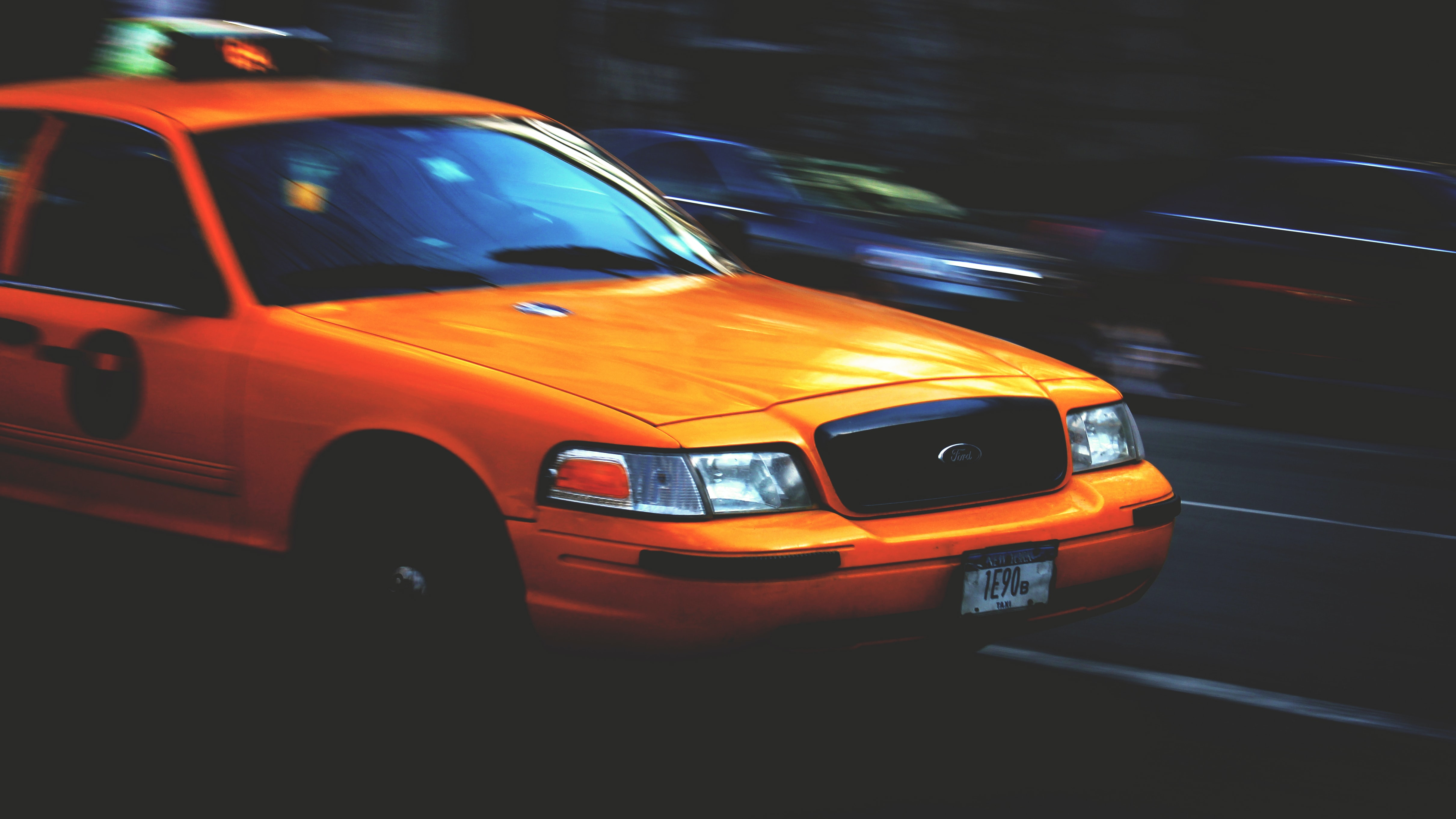 Yellow Ford Taxi Cab driving against blurred background
