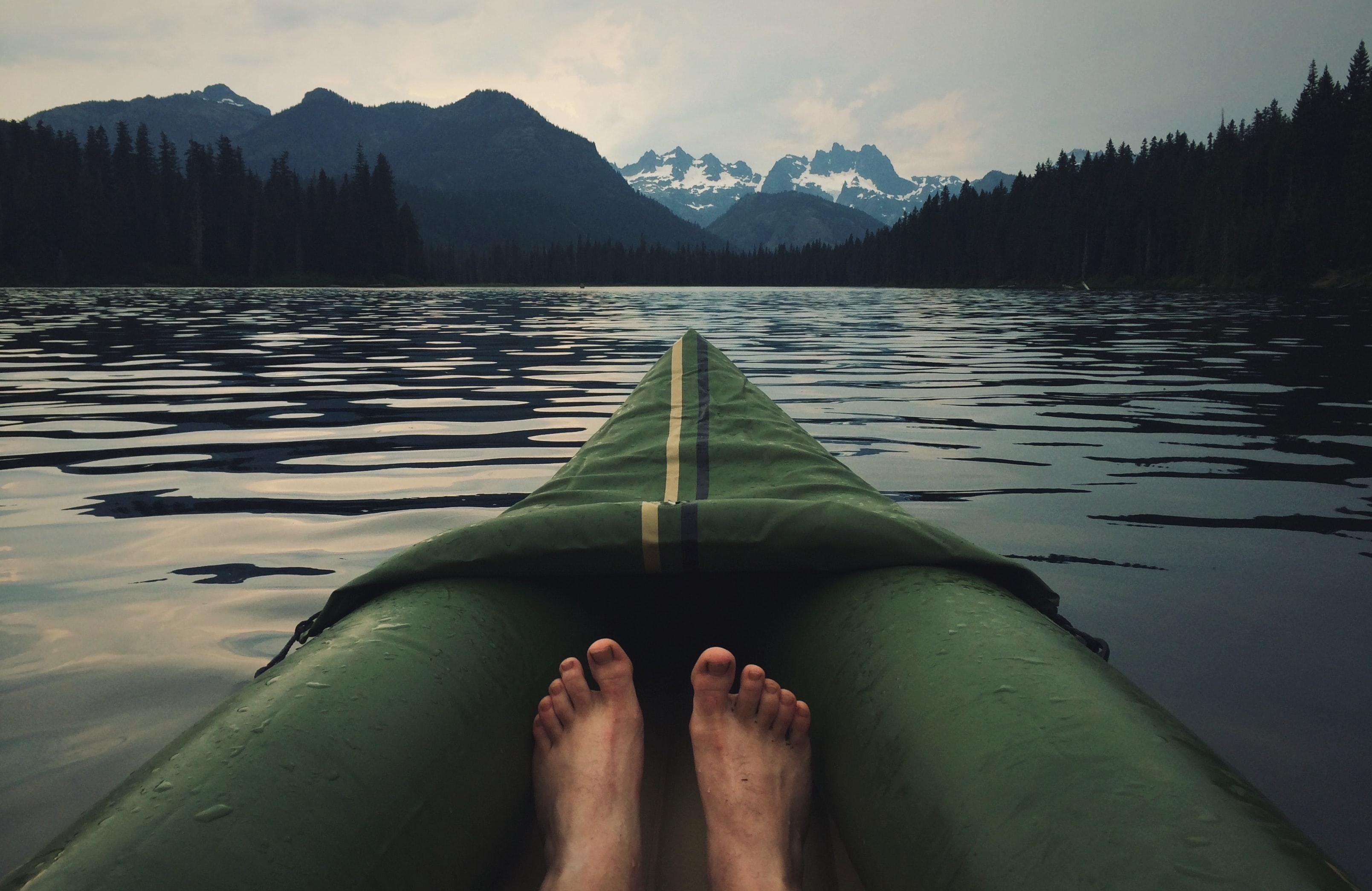 The view of a person's feet and the front of their canoe on a lake