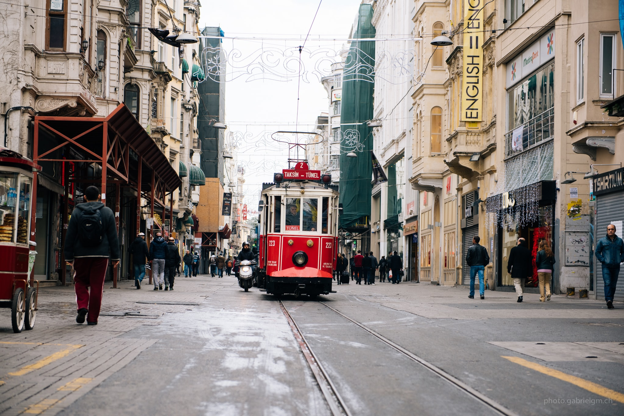 Red cable car in road with people and buildings on either side