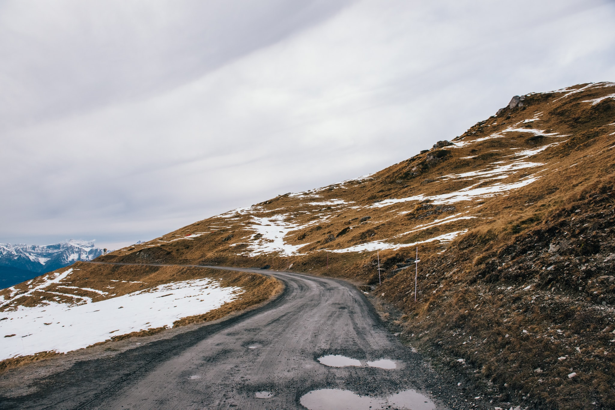 A rough mountain road curves around a wilderness with patches of snow