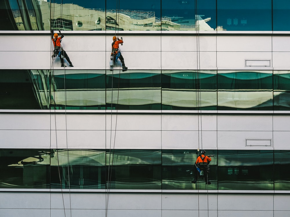 man cleaning white building