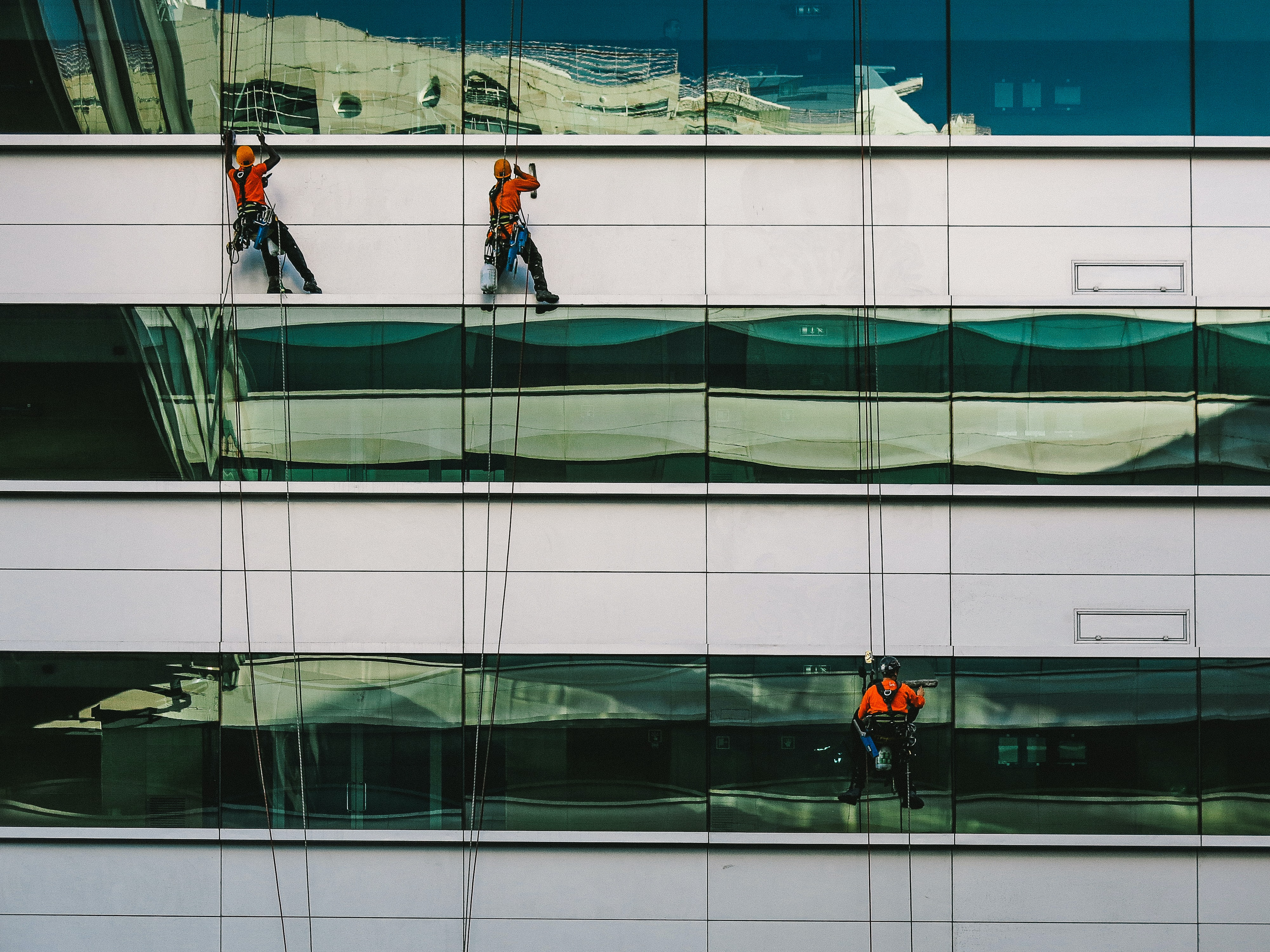 Three window cleaners on ropes on an office building facade