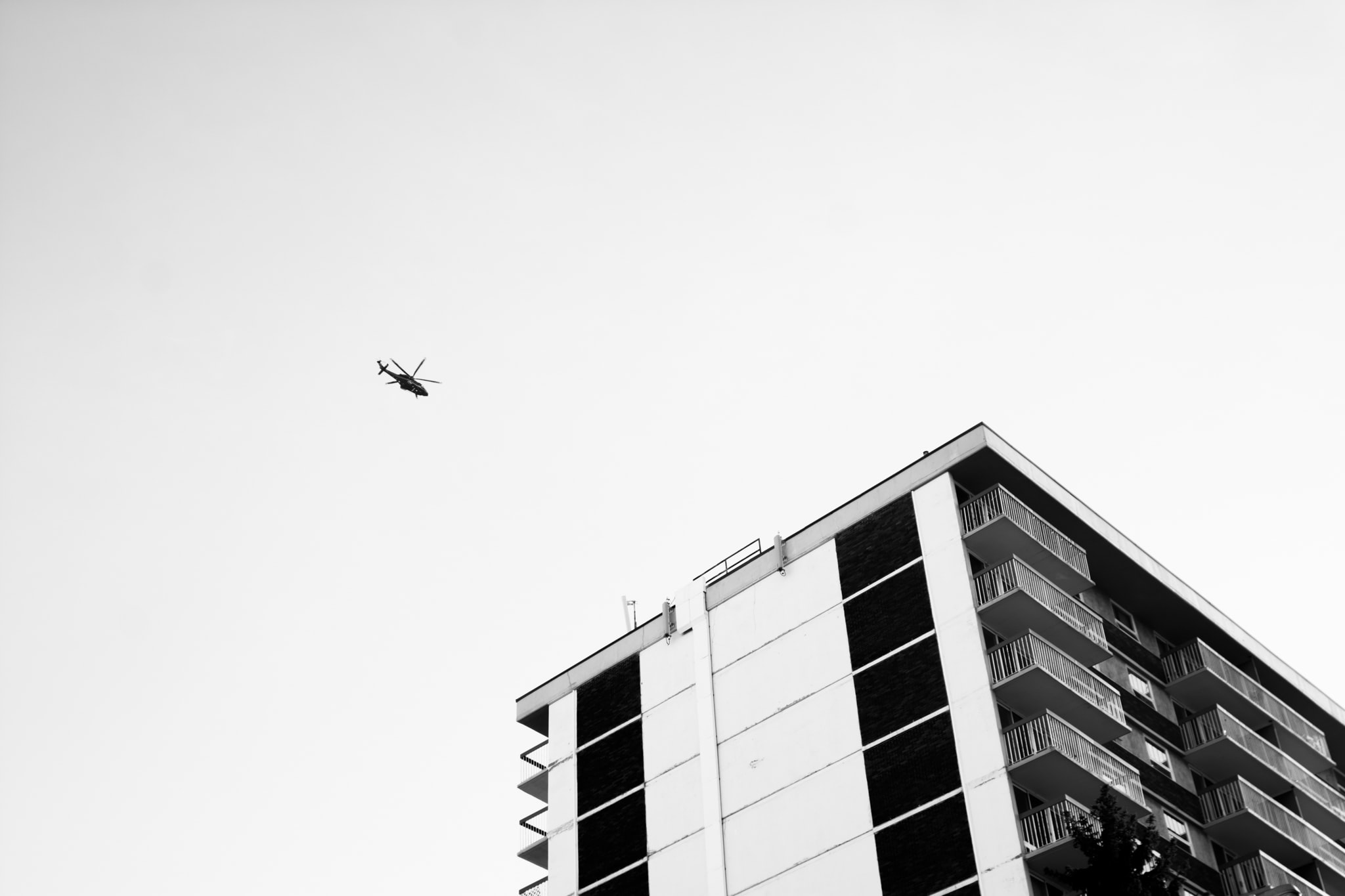 A helicopter is flying above an apartment building.