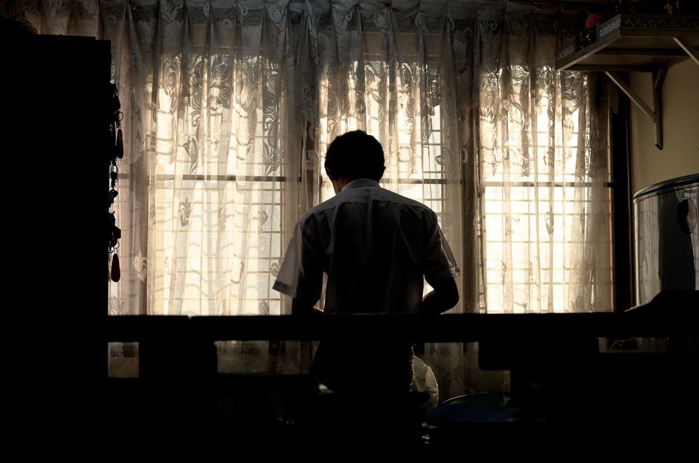 man wearing white collared shirt near window