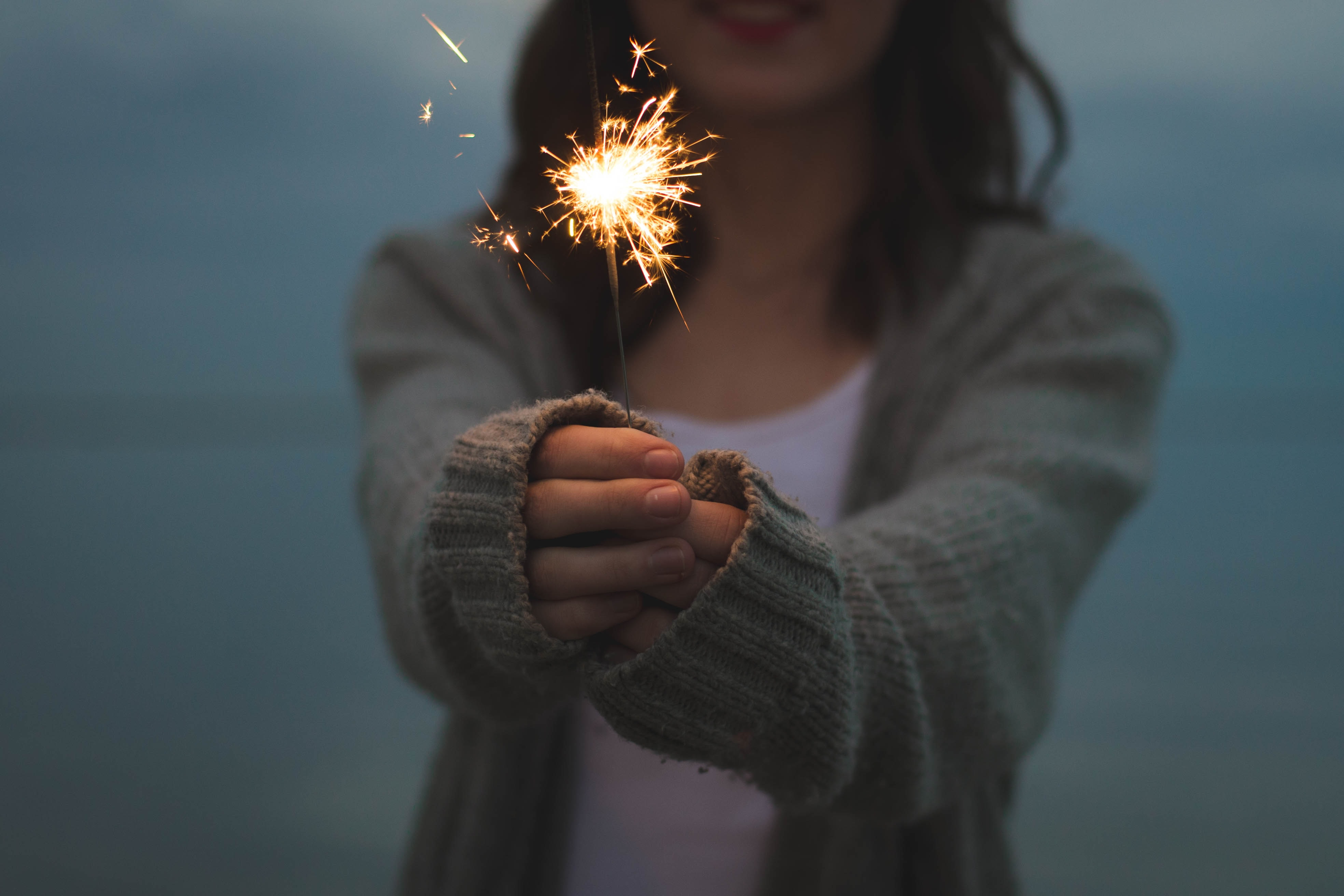 focus photo of a woman holding sparklers